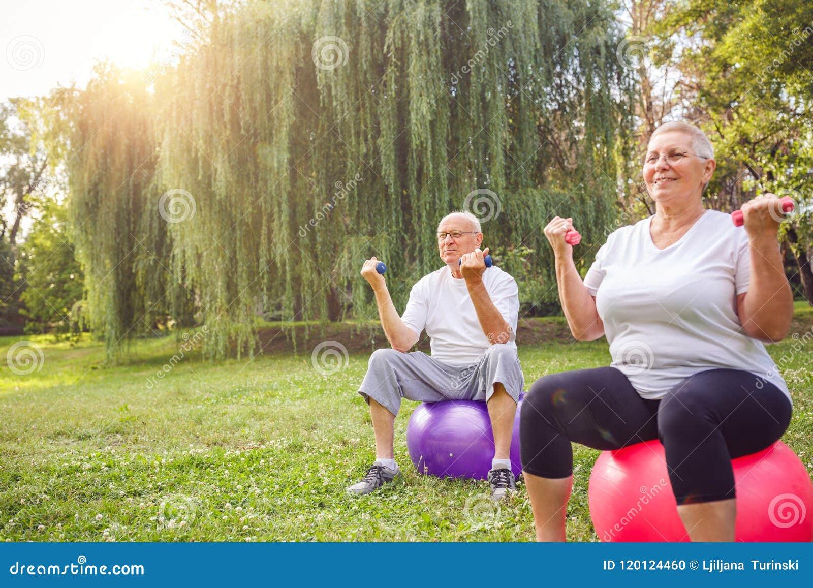 Les couples mûrs s exercent ensemble sur la boule de forme physique en parc
