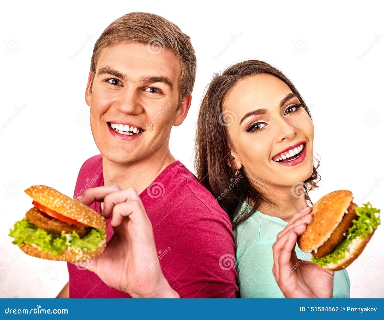 Les couples mangent l hamburger Les femmes et l homme prennent les aliments de préparation rapide