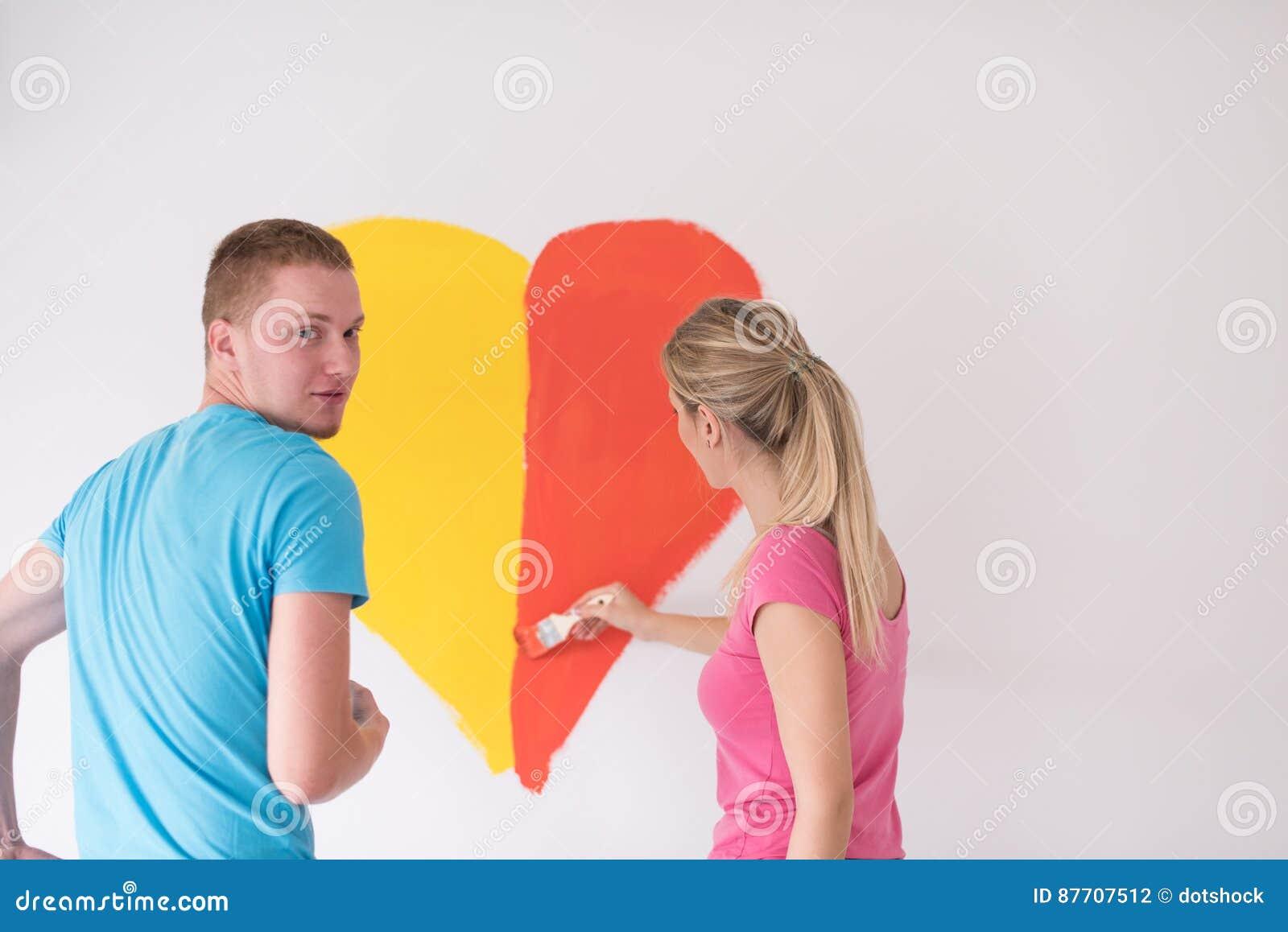 Les couples peignent un coeur sur le mur
