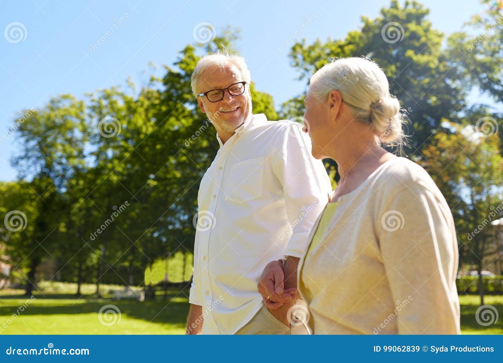 Les couples supérieurs heureux marchant à la ville d été se garent