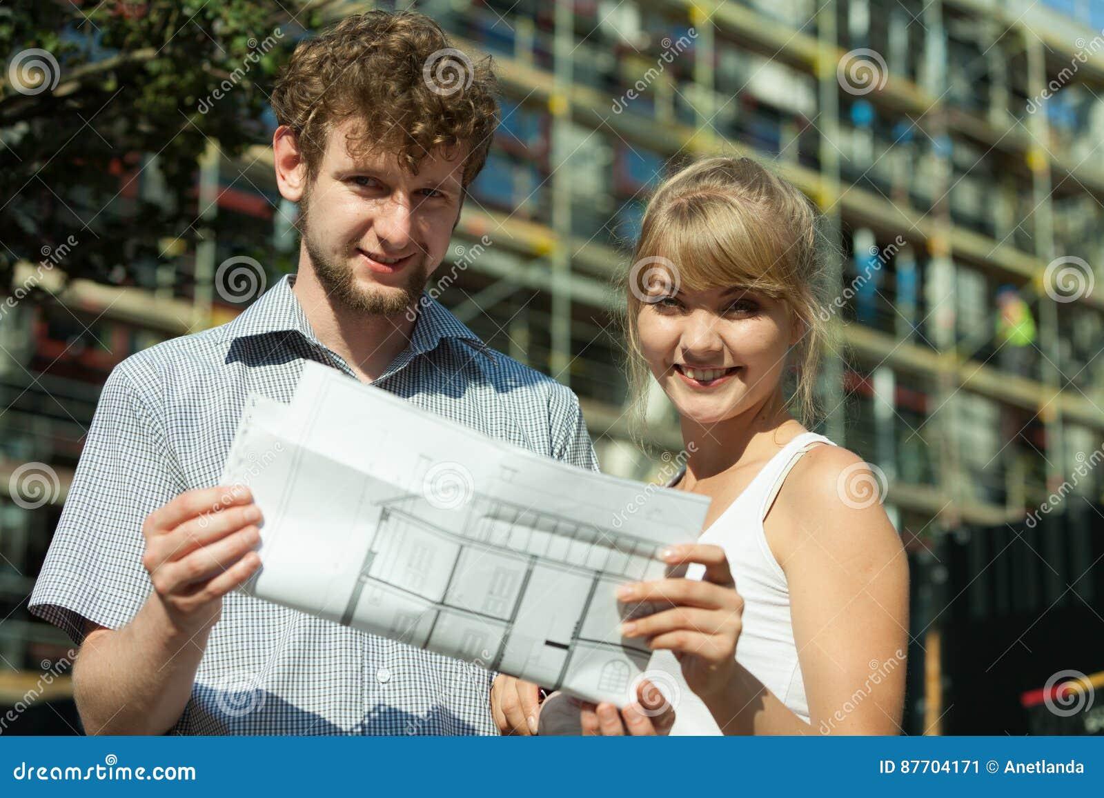 Les couples sur l avant de la nouvelle maison avec le modèle projettent