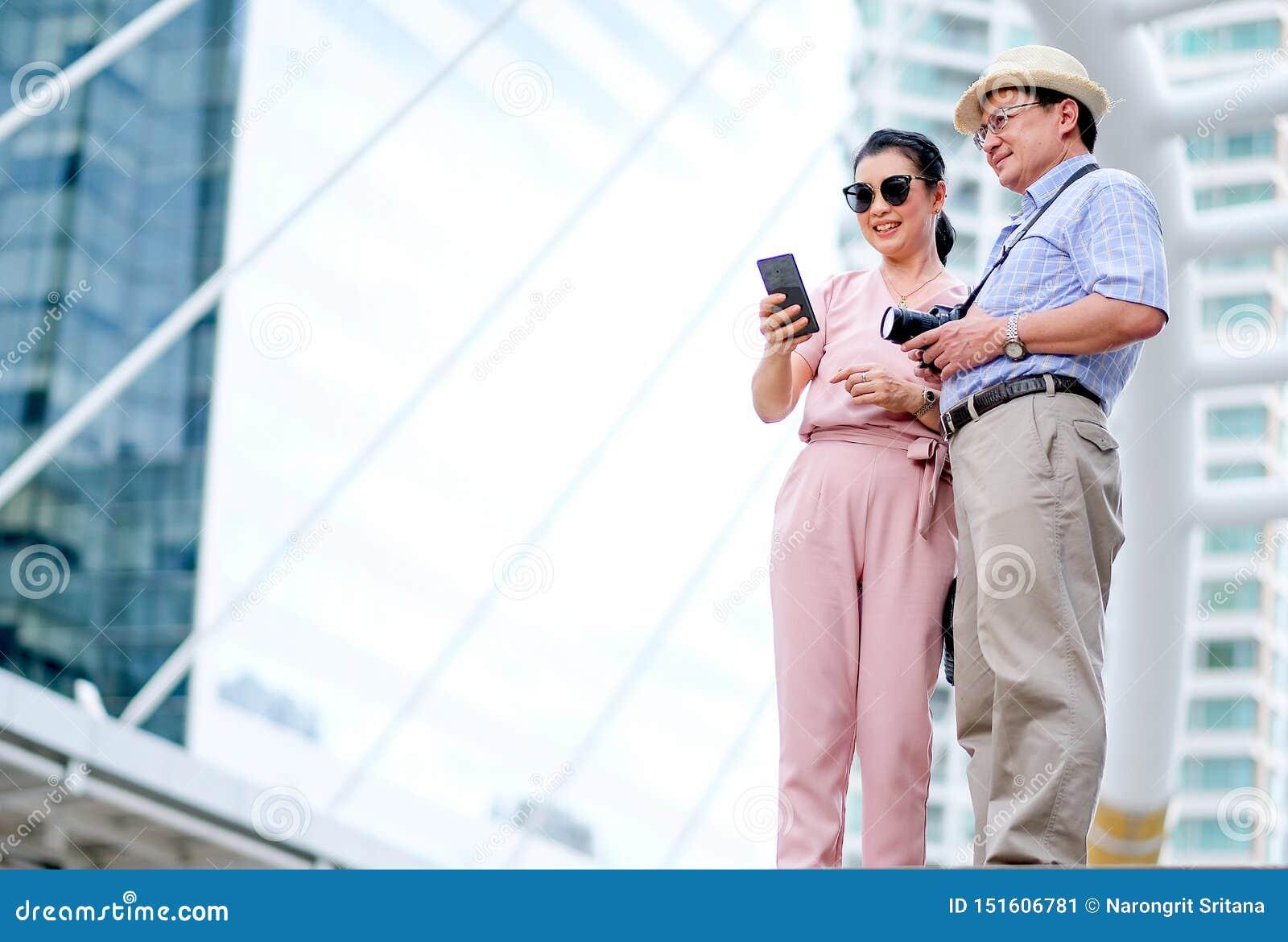 Les couples vieil du touriste asiatique d homme et de femme regardent le téléphone portable et le sourire Cette photo également c
