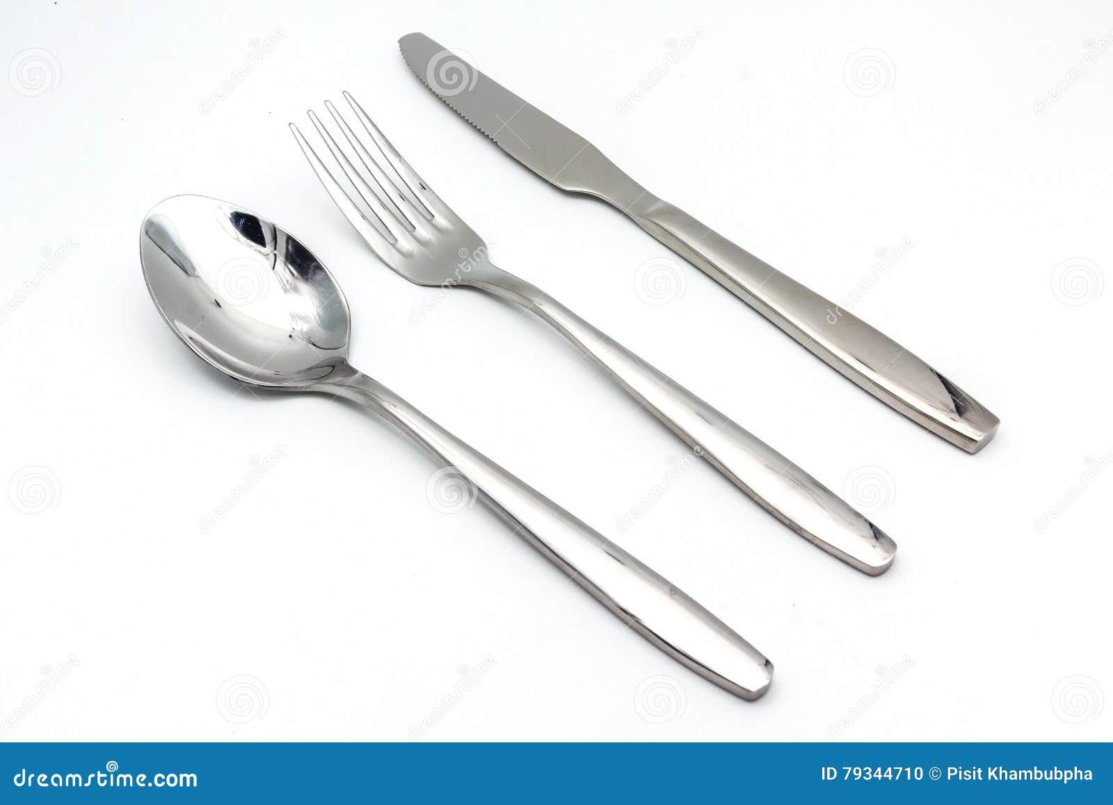 Les couverts ont placé avec la fourchette, le couteau et la cuillère d isolement sur le fond blanc