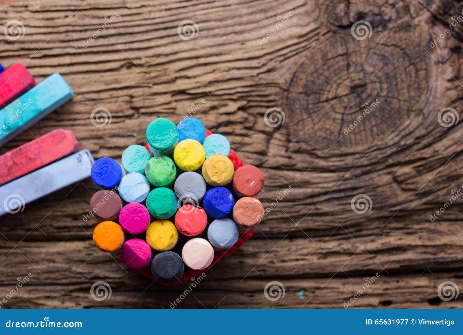 Les crayons et le colorant en pastel époussettent sur le vieux fond en bois