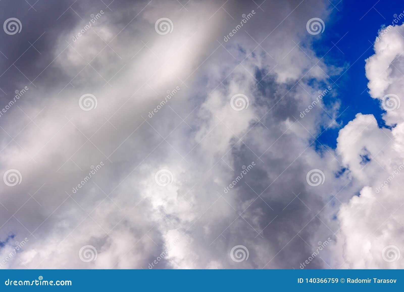 Les cumulus blancs luxuriants nagent à travers le ciel bleu