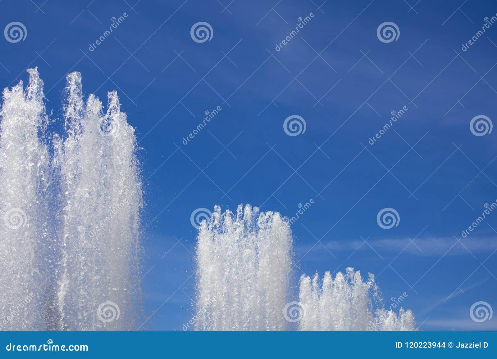 Les dessus de la grande fontaine voyage en jet le jaillissement vers le haut contre le ciel bleu