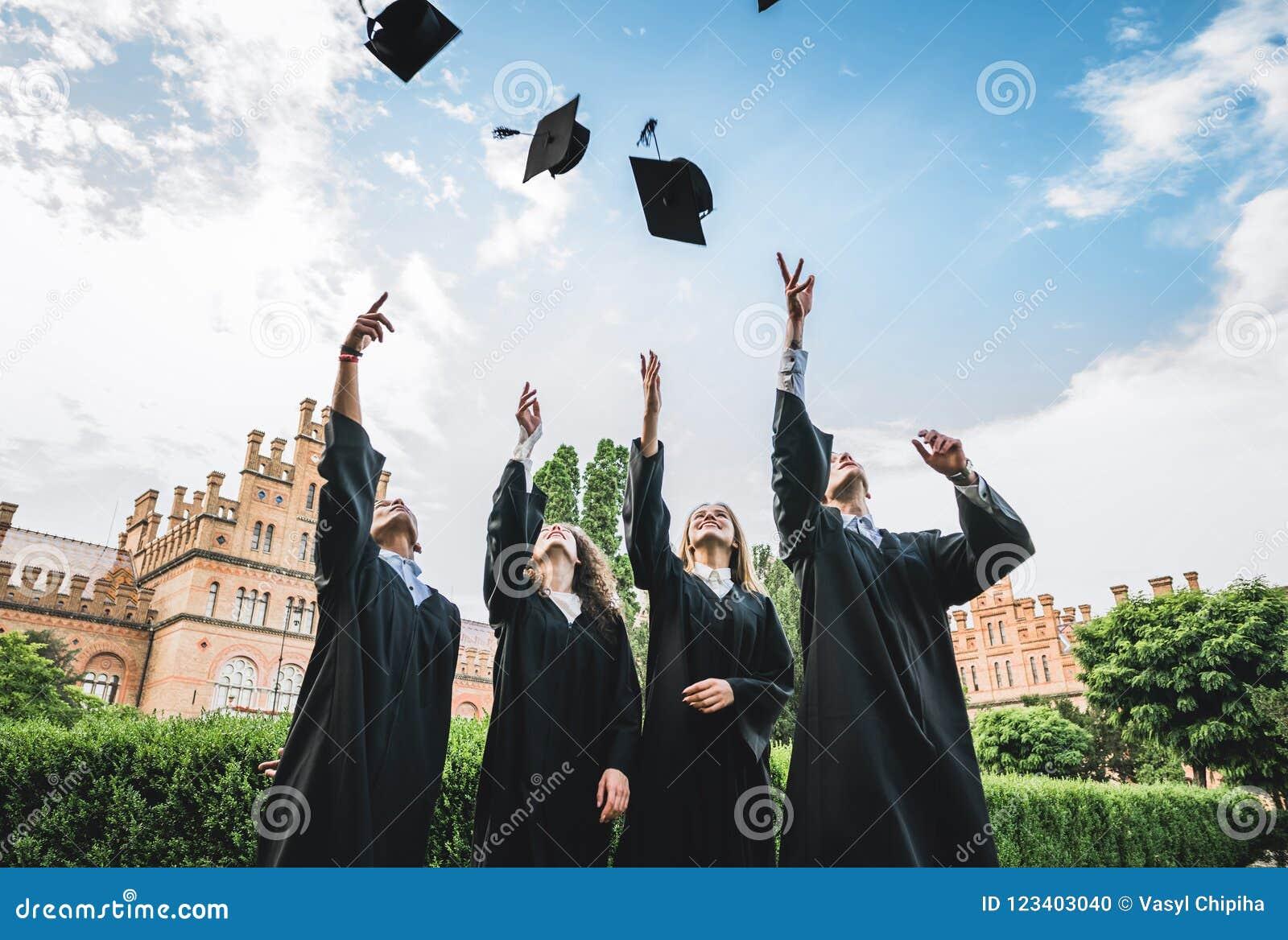 Les diplômés près de l université jettent des chapeaux dans le ciel