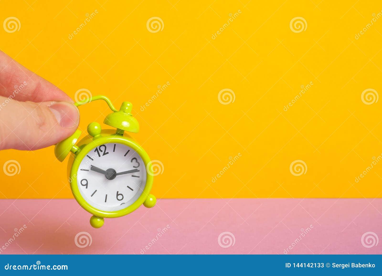 Les doigts tiennent une horloge de vert de cru sur un fond jaune