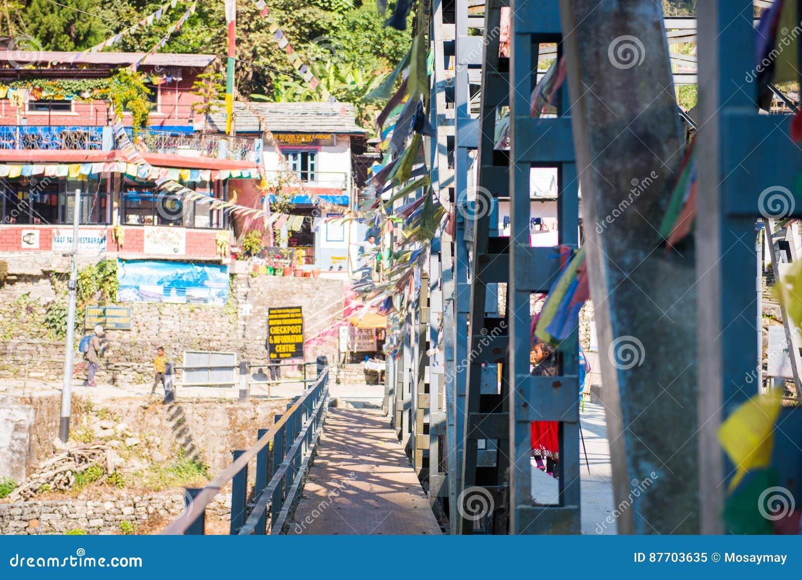 Les drapeaux colorés de prière accrochent sur le pont de rivière au Népal
