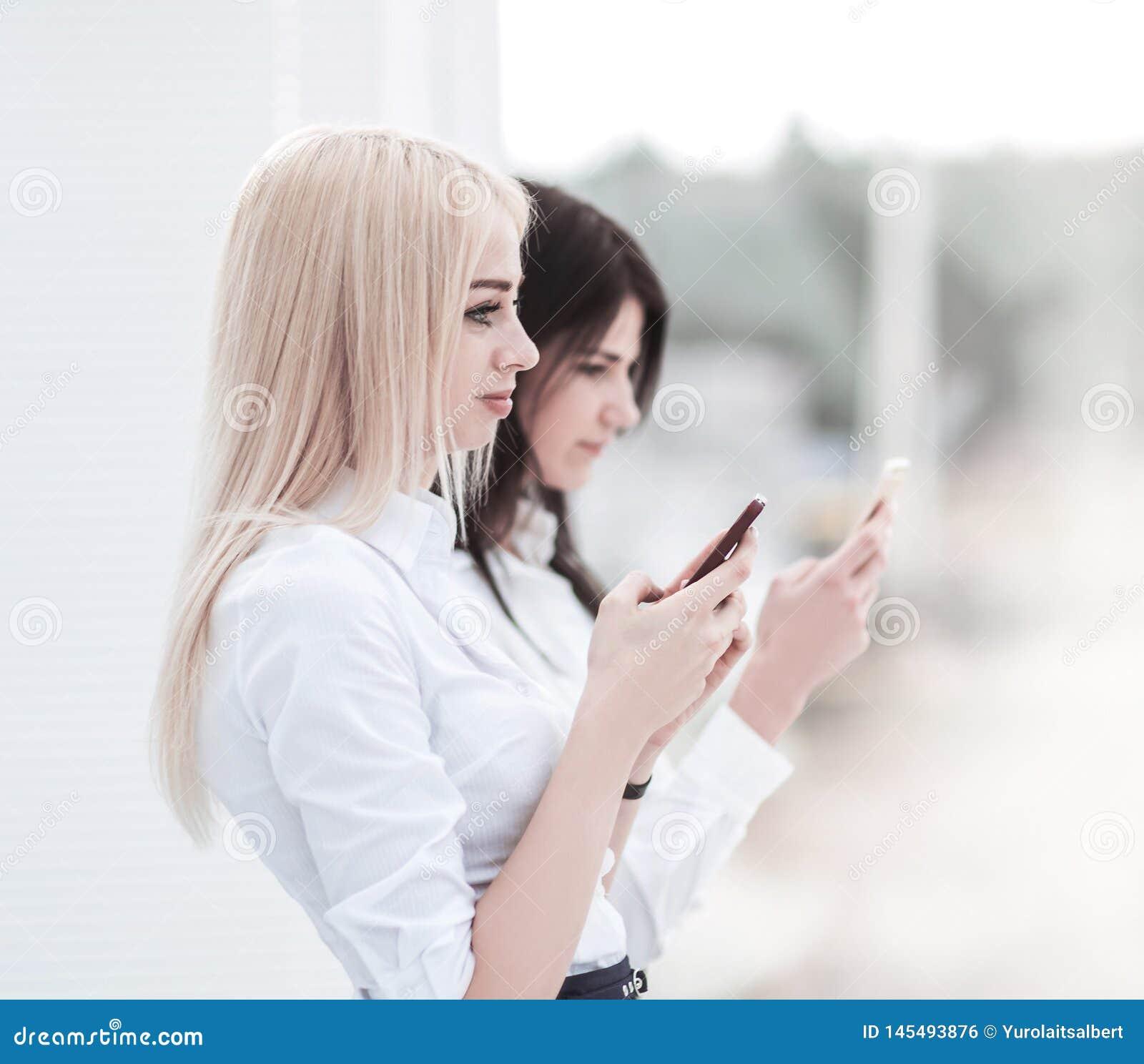 Les employ?es de jeunes femmes de la soci?t? ?changent l information sur un smartphone