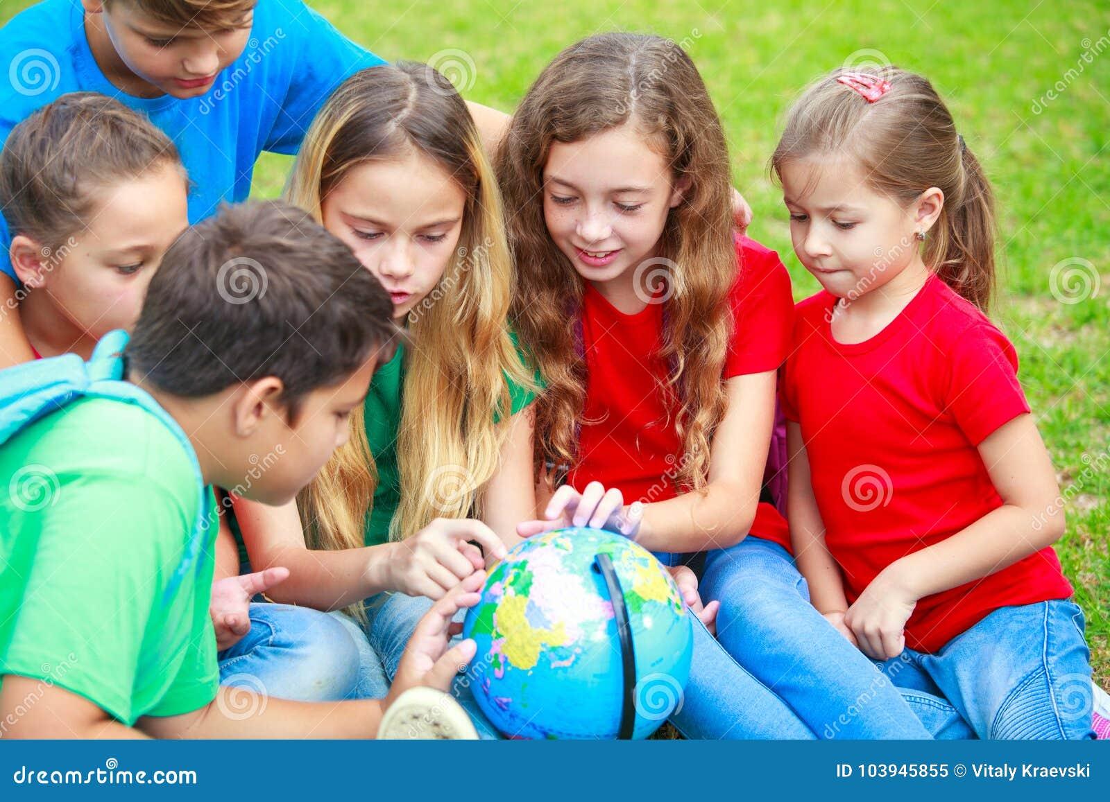 Les enfants avec un globe apprennent la géographie