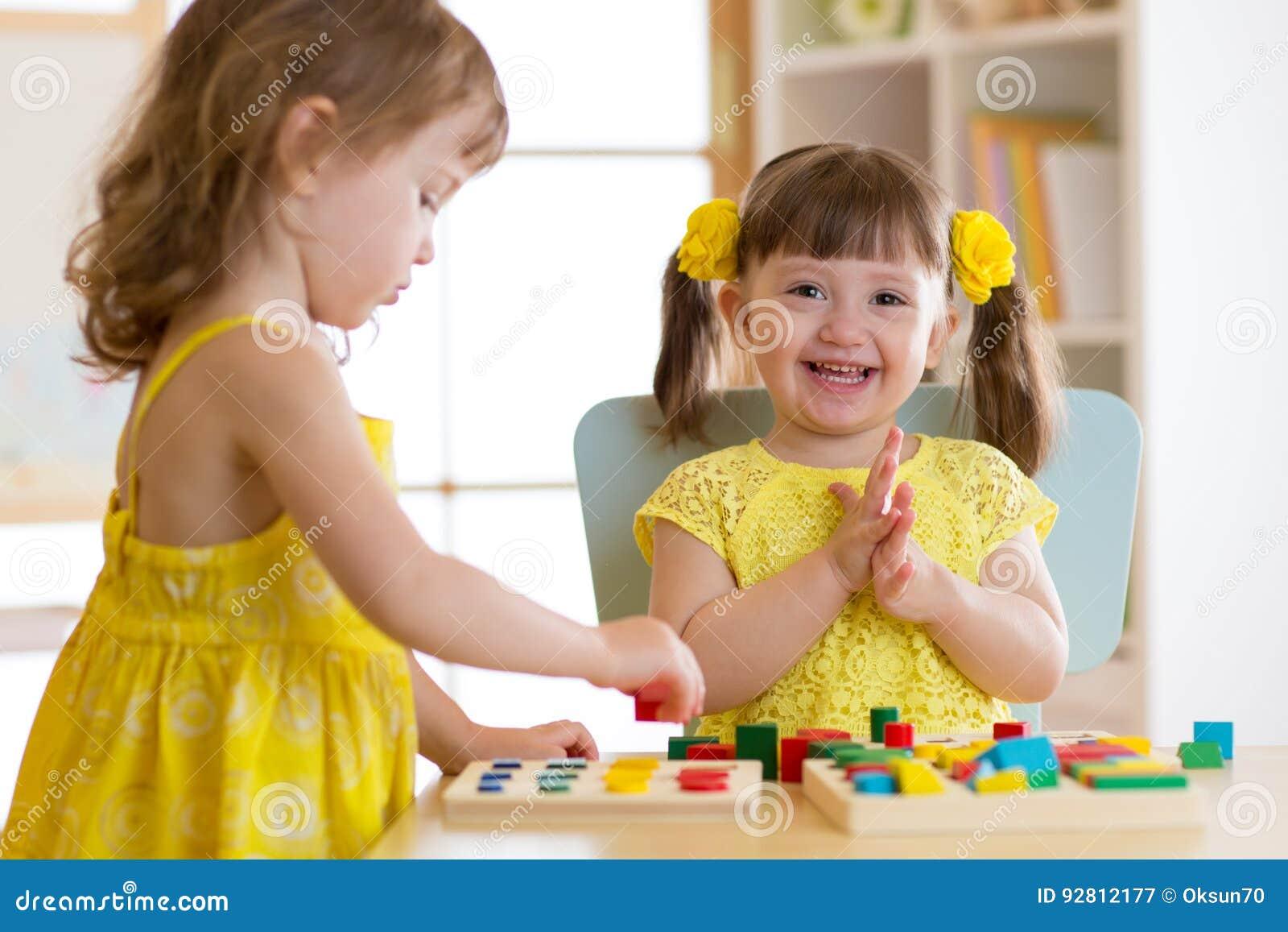 Les enfants d enfants jouent avec les jouets éducatifs, arrangeant et assortissant des couleurs et des formes Étude par l intermé