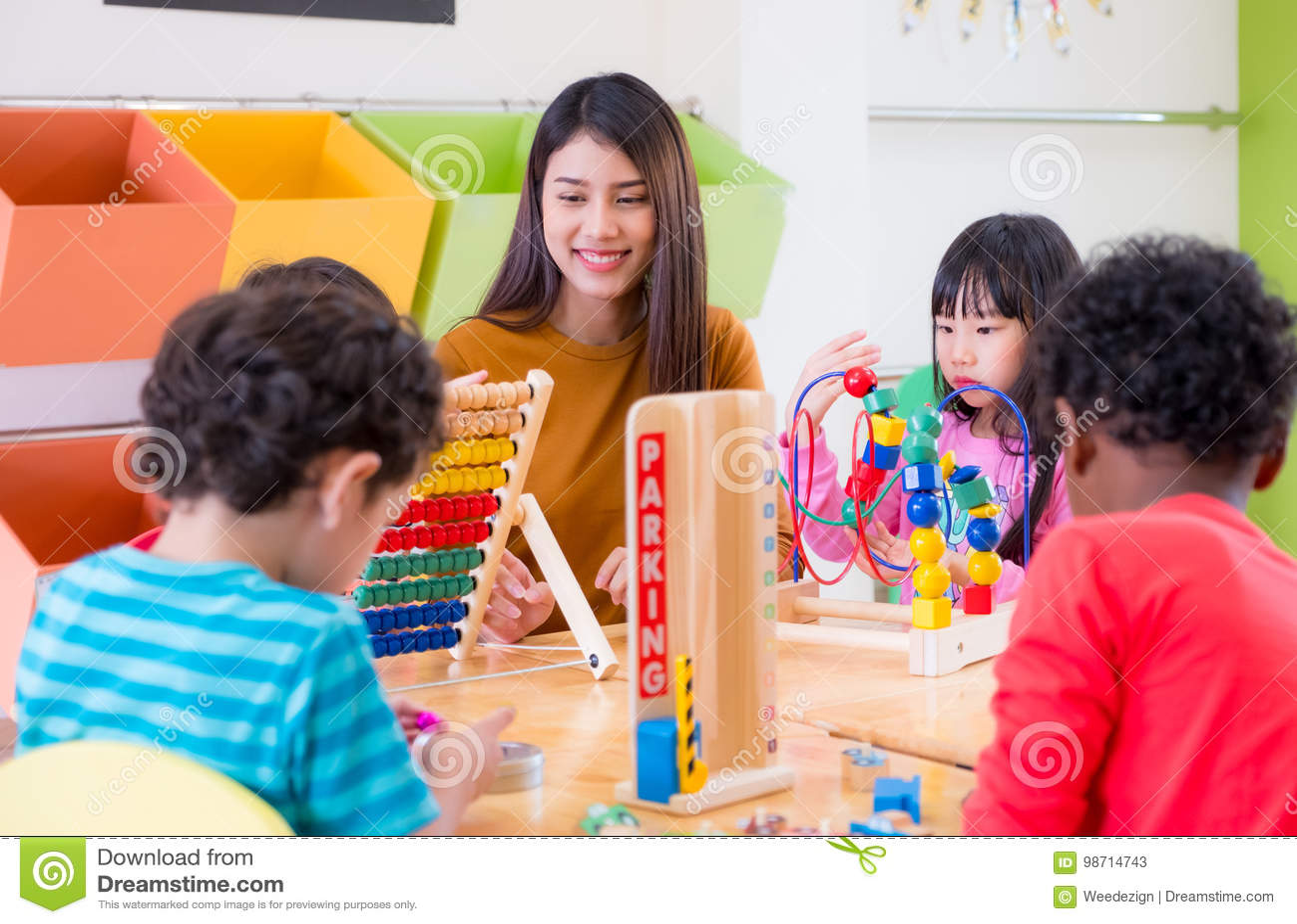Les enfants de enseignement asiatiques de métis de professeur féminin jouent le jouet dans le classr