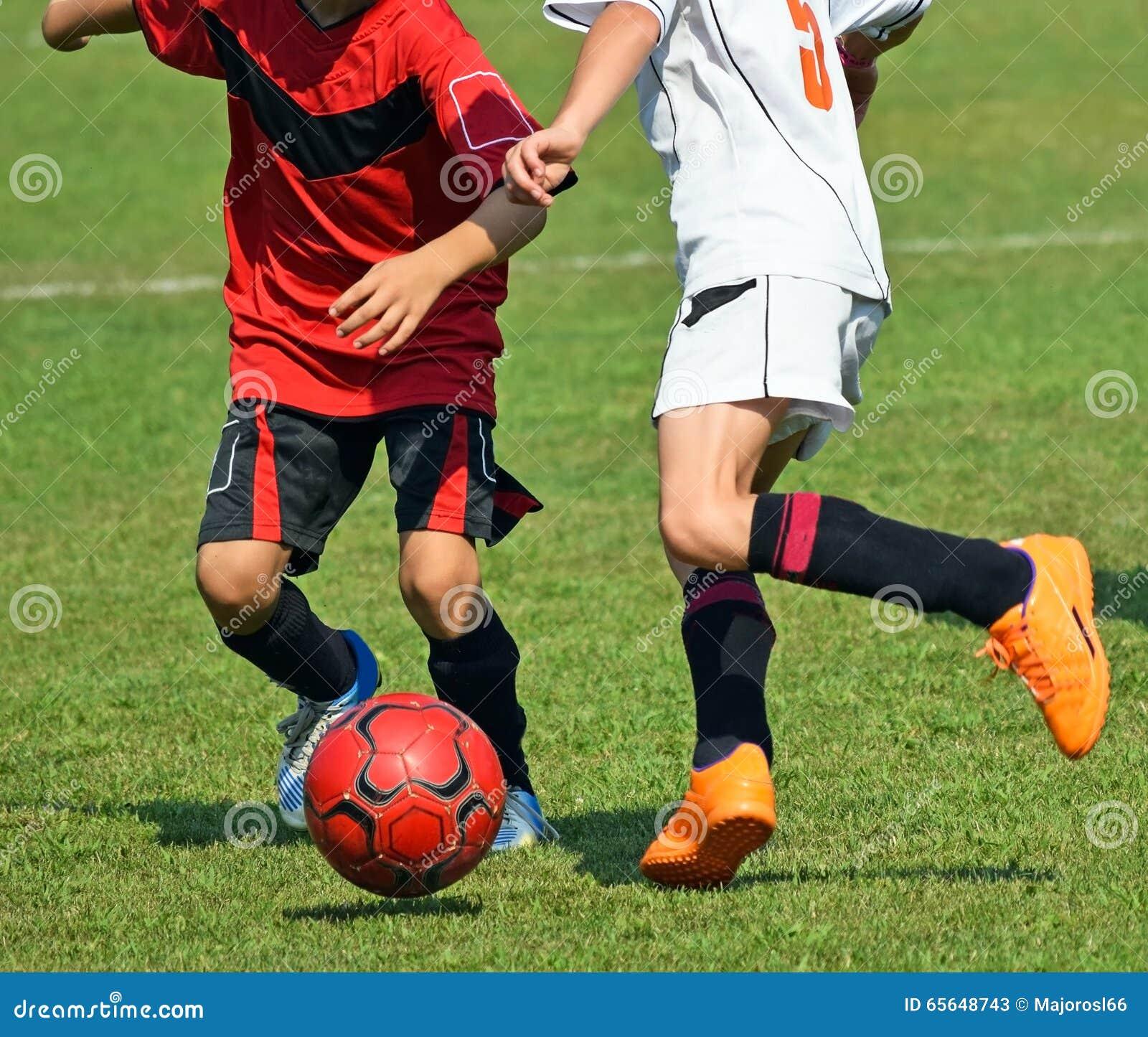 Les enfants donnent un coup de pied la boule un match de football