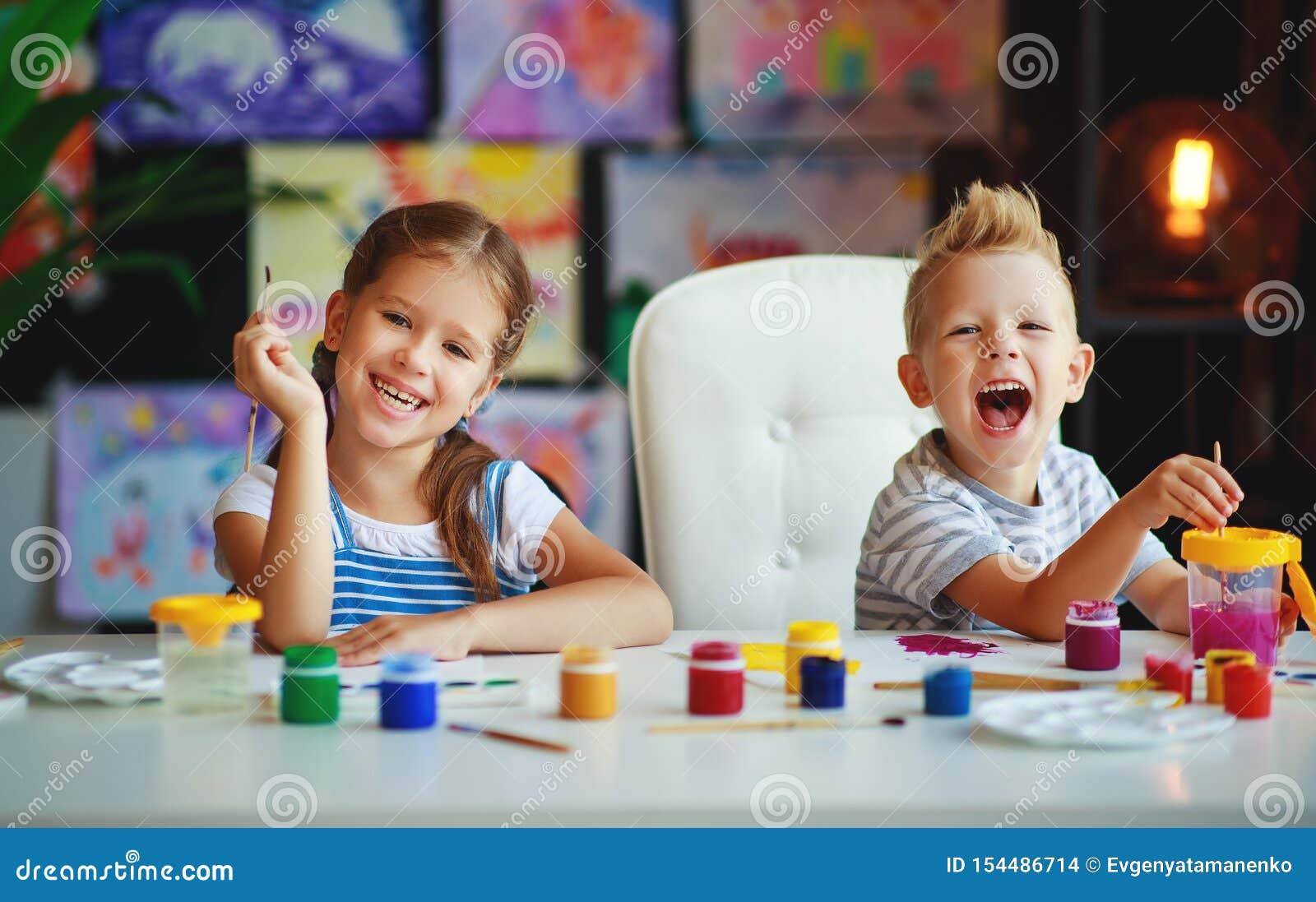 Les enfants drôles fille et garçon dessine rire avec la peinture
