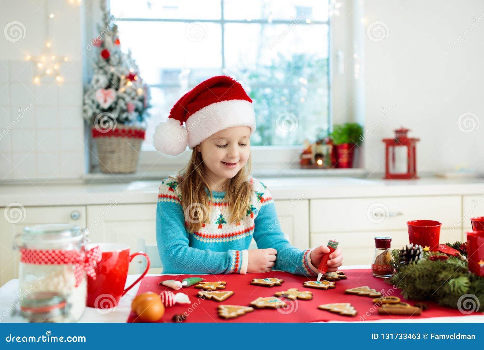 Les enfants font des biscuits cuire au four de Noël Enfant dans le chapeau de Santa faisant cuire, décorant le bonhomme en pain d