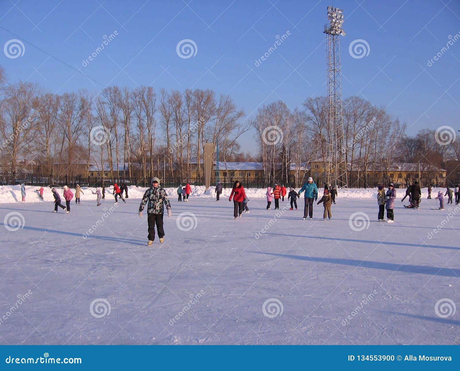Les enfants gais montent pendant l hiver patinant sur la grande piste
