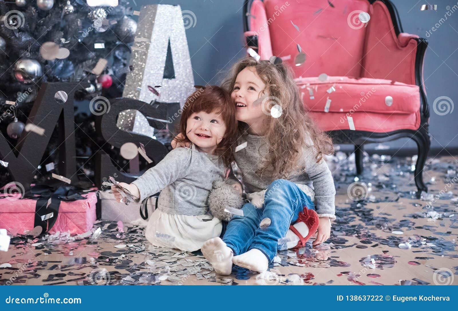 Les enfants jettent des confettis et s asseyent sur un plancher près d un sapin