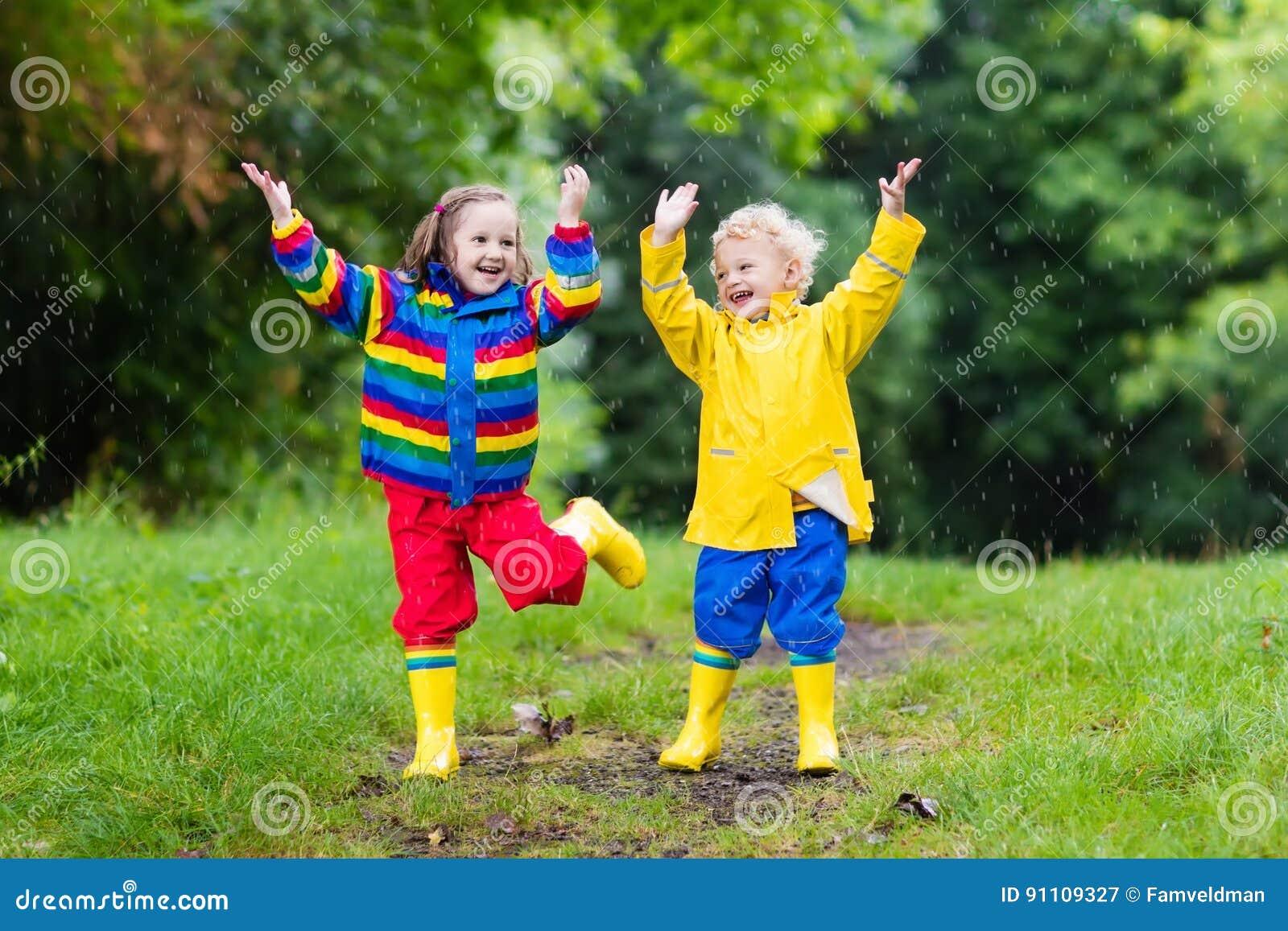 Les enfants jouent dans la pluie et le magma en automne
