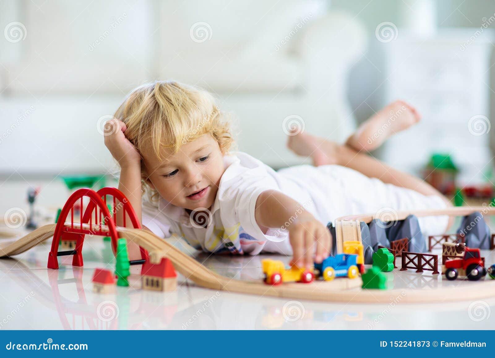 Les enfants jouent le chemin de fer en bois Enfant avec le train de jouet
