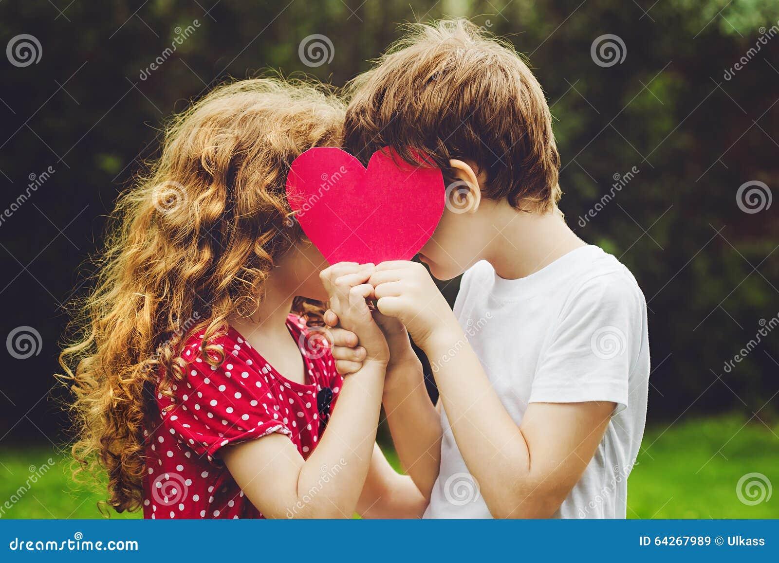 Les enfants mignons tenant le coeur rouge forment en parc d été valentines