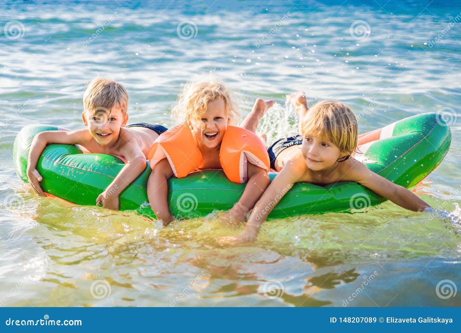 Les enfants nagent en mer sur un matelas gonflable et avoir l amusement