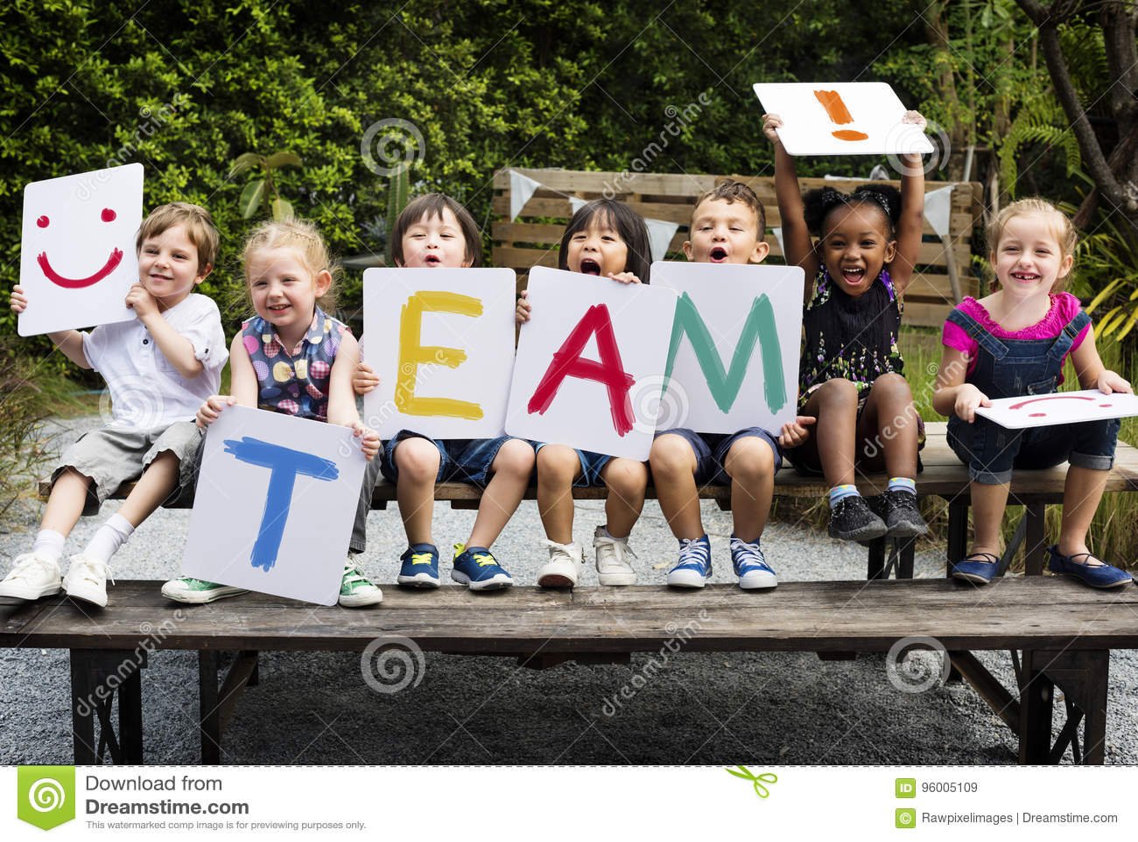 Les enfants s asseyent sur la table en bois tenant une équipe de mot