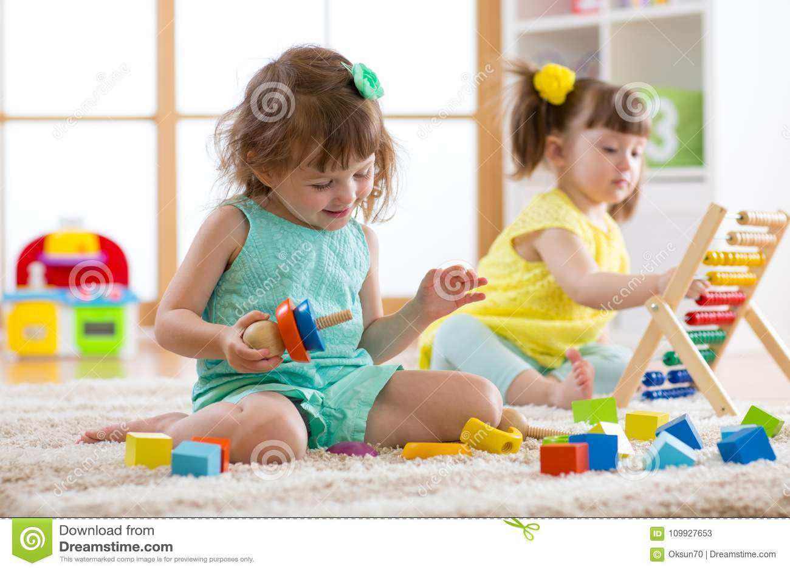 Les enfants s engagent dans la garde Deux enfants d enfant en bas âge jouant avec les jouets éducatifs dans le jardin d enfants