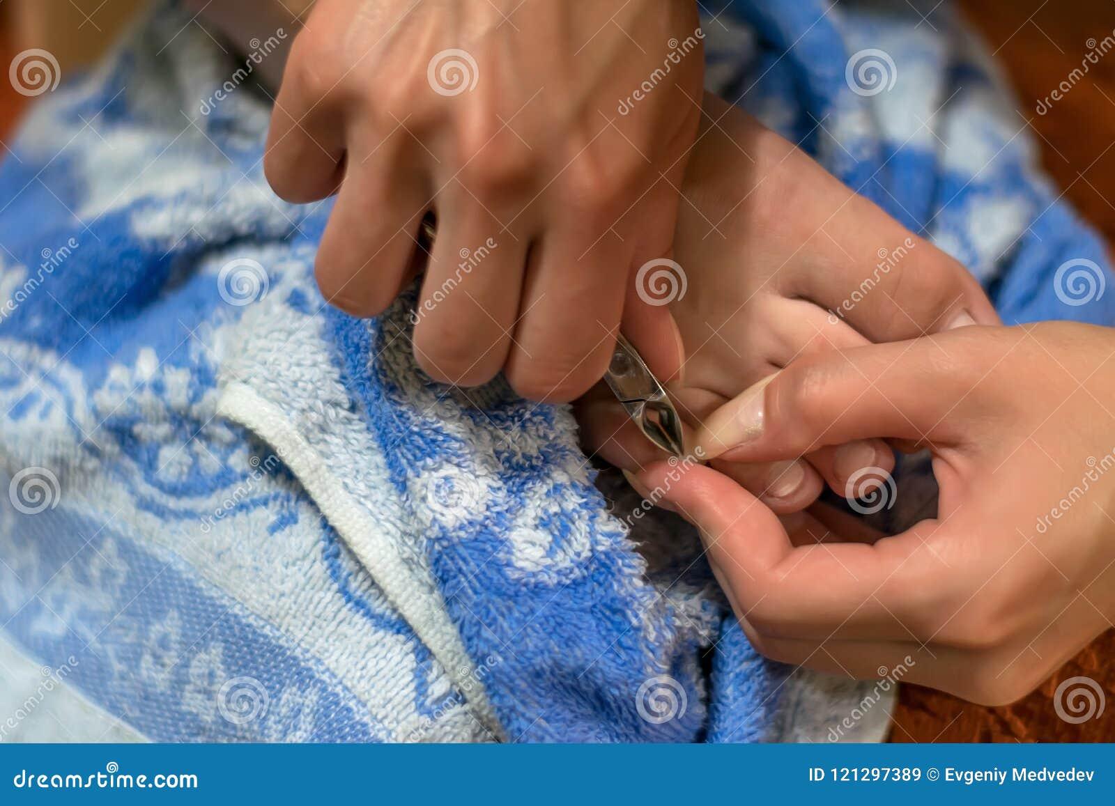 Les entretenir de fille des doigts d ongles à la maison Nettoyez les cuticles avec des pinces de clou pour le manicur