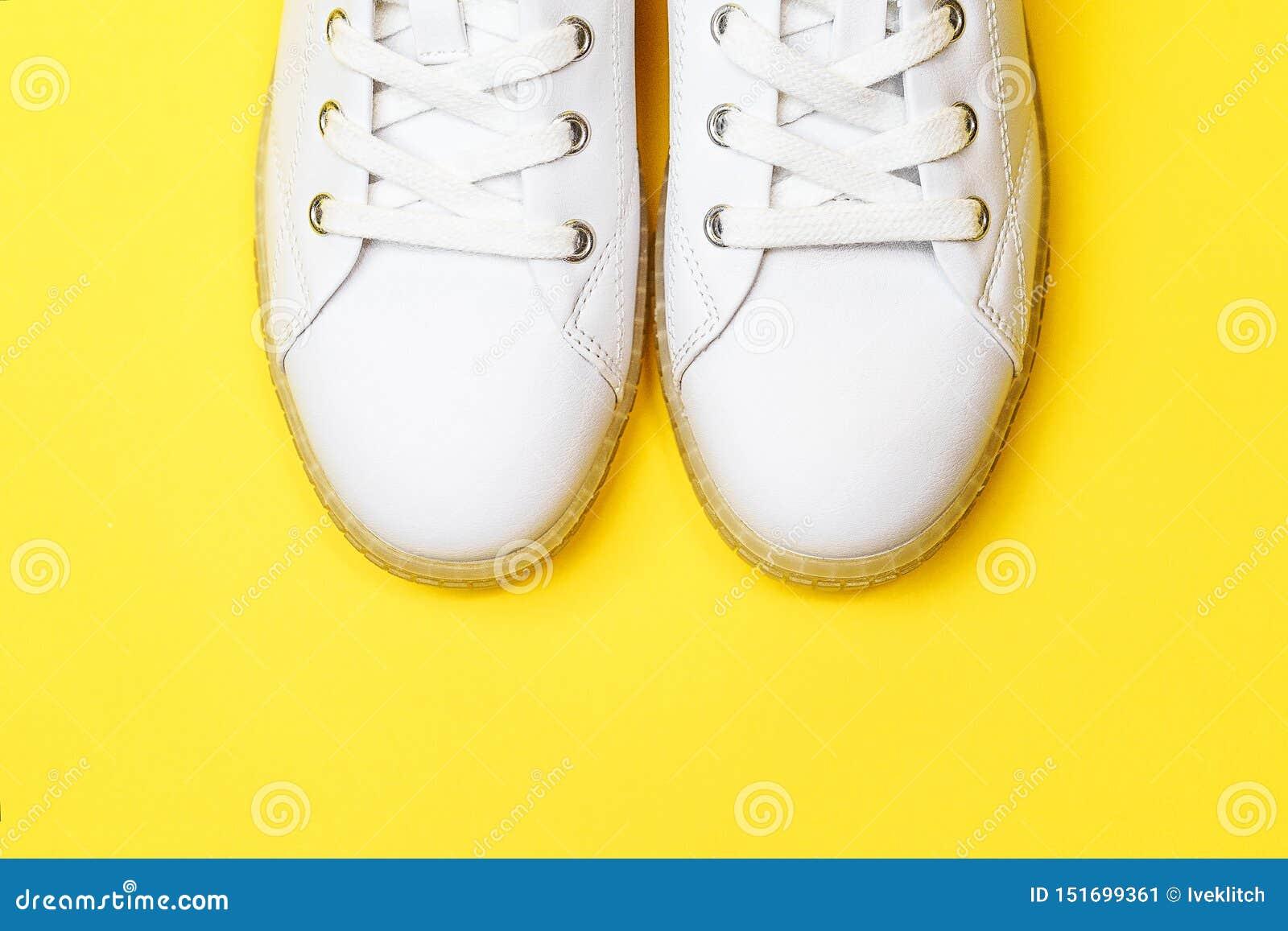 Les espadrilles blanches se trouvent sur un fond jaune en pastel