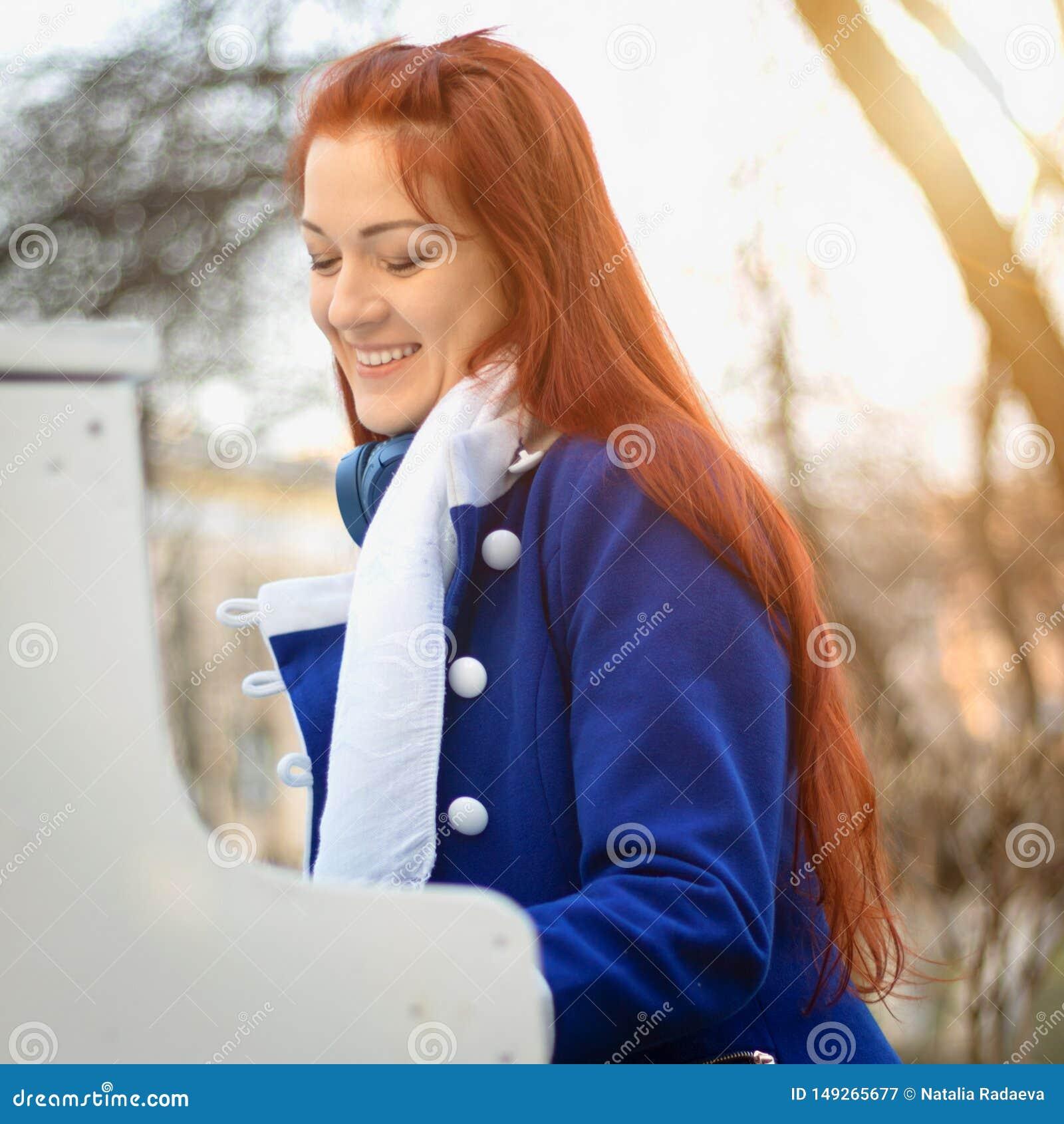 Les femmes caucasiennes europ?ennes de fille avec les cheveux rouges sourit et joue le piano en parc au coucher du soleil Musique