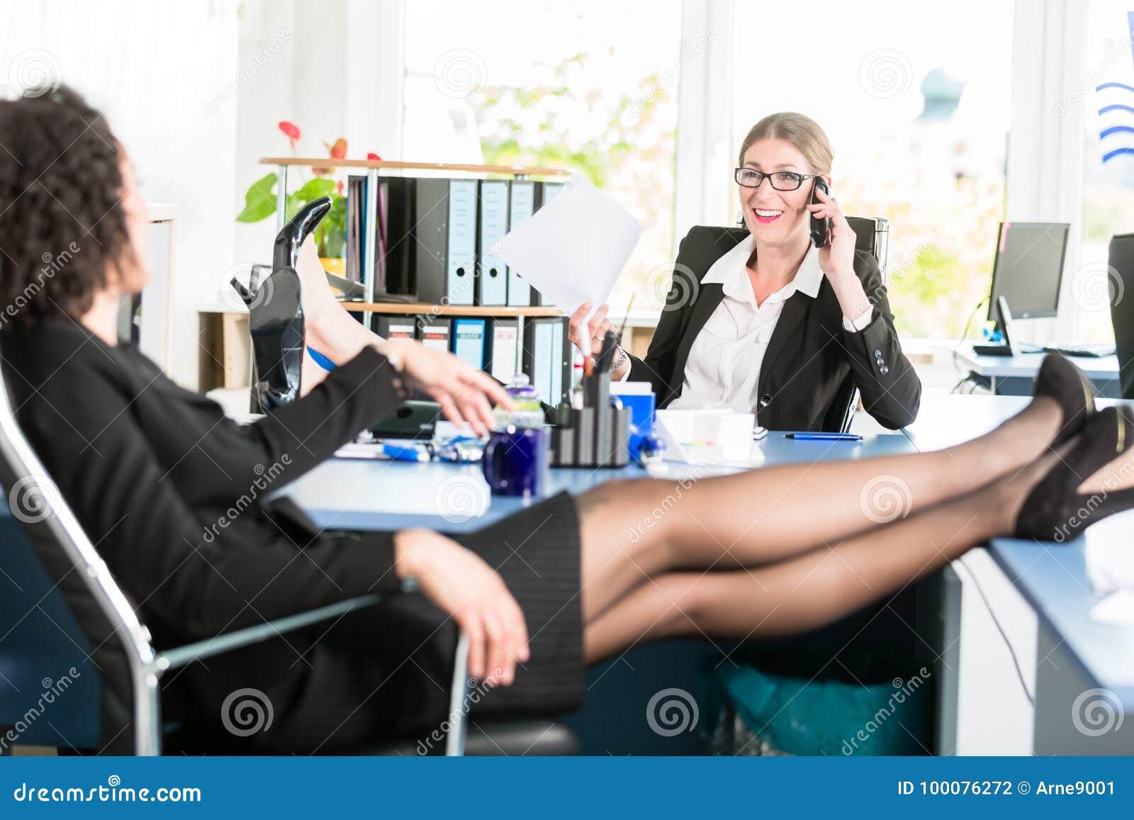 Les femmes d affaires détendent avec leurs pieds sur le bureau au