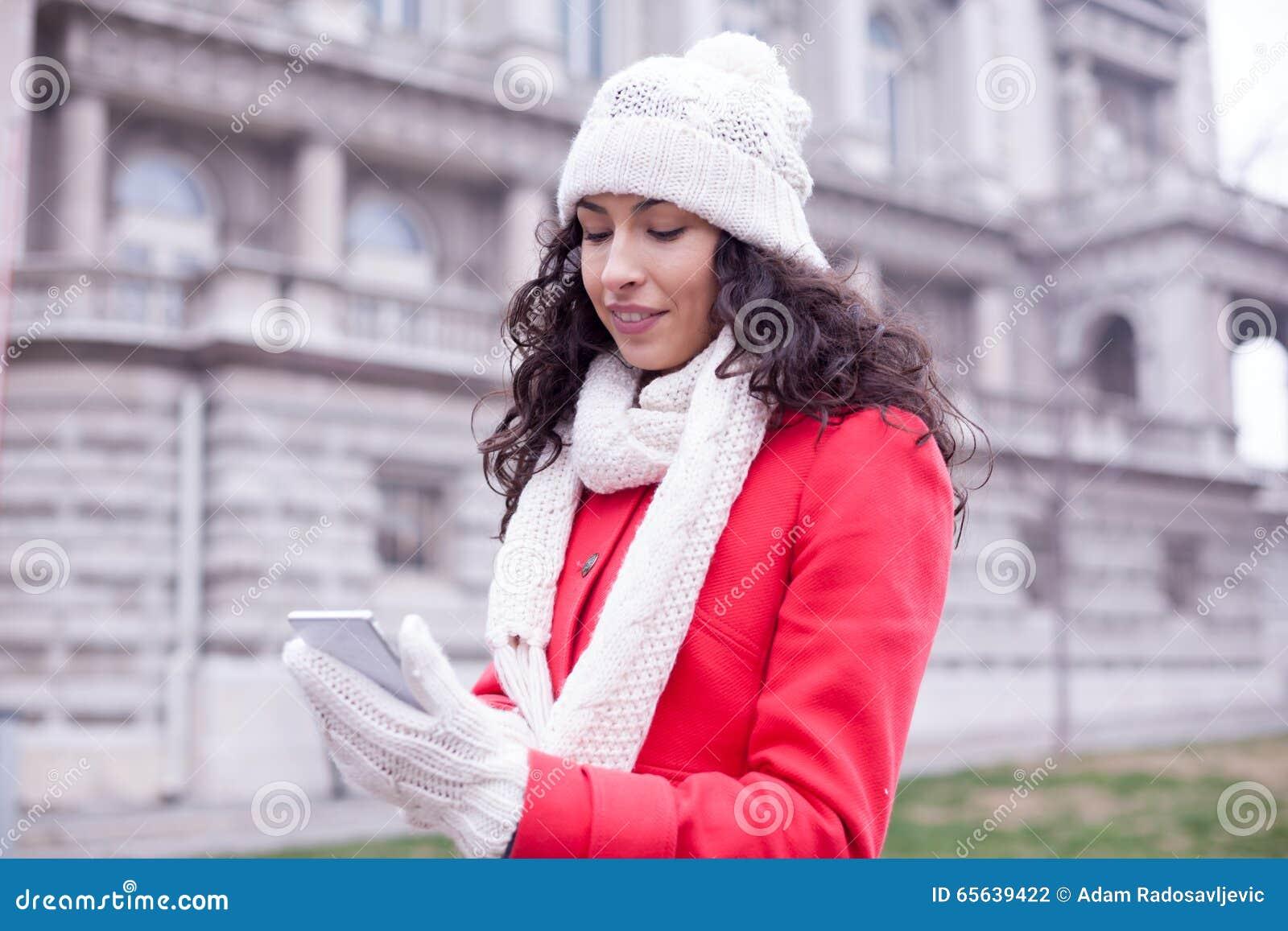 Les femmes de sourire ont lu des actualités de mode sur le comprimé de smartphone