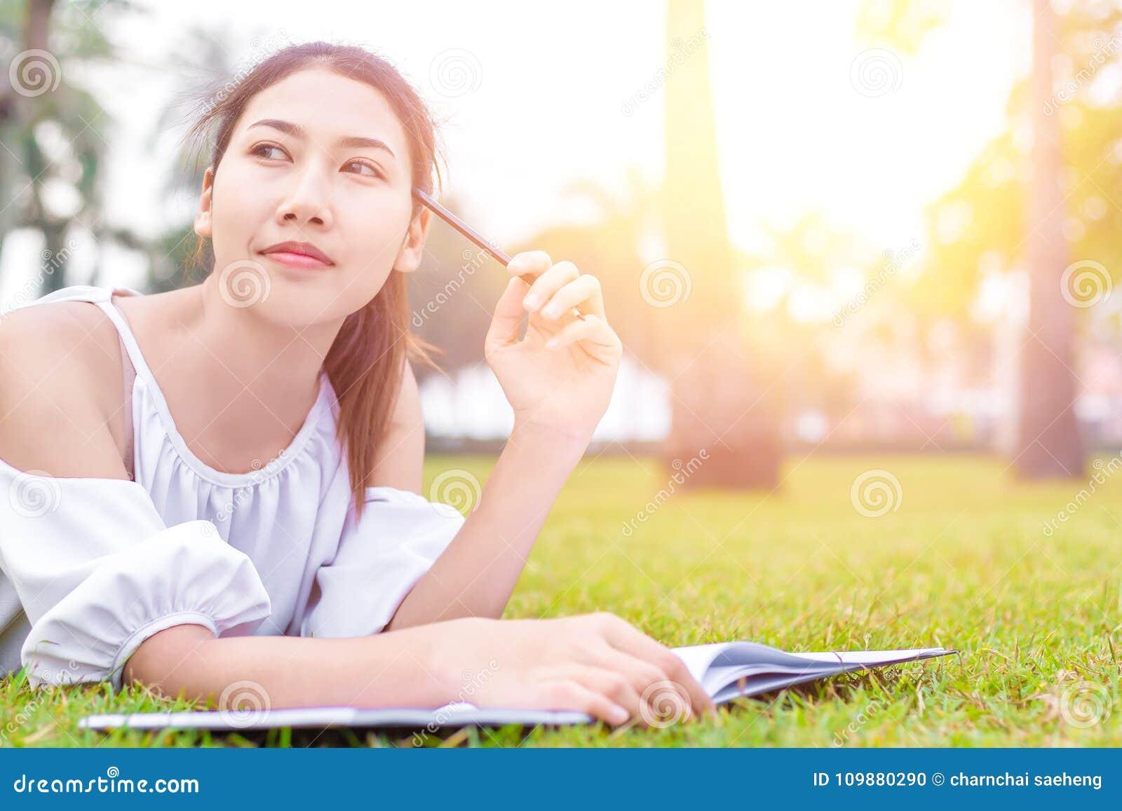 Les femmes est sur l herbe et beau Elle pense que… vous le travail doit trouver ce qui ! le livre est sur l herbe elle portent la