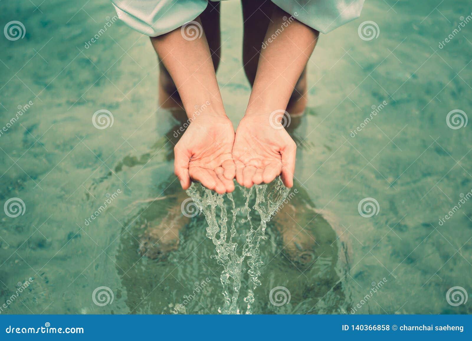 Les femmes se tiennent dans l eau et les mains cherchent l eau et avoir l éclaboussure de l eau