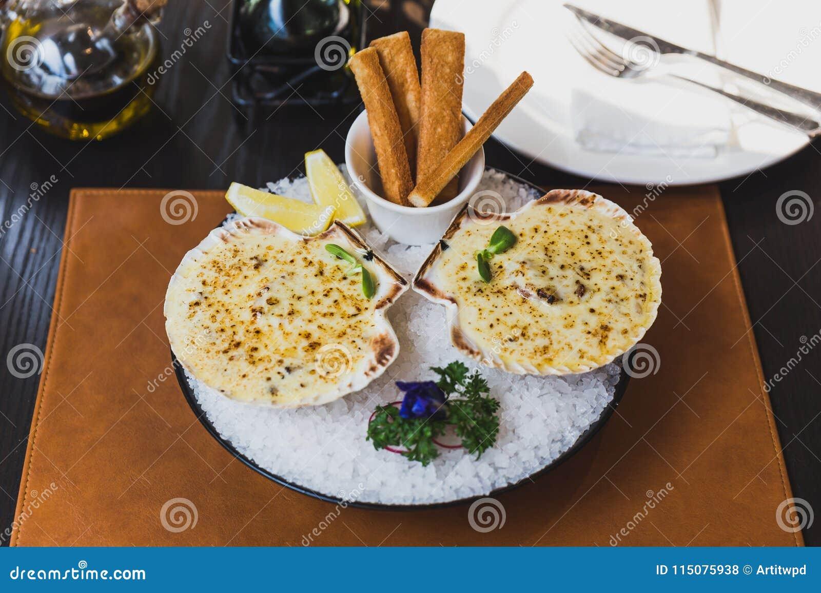 Les festons cuits au four avec du fromage ont servi avec les batons découpés en tranches de citron et de pain sur la cuvette avec