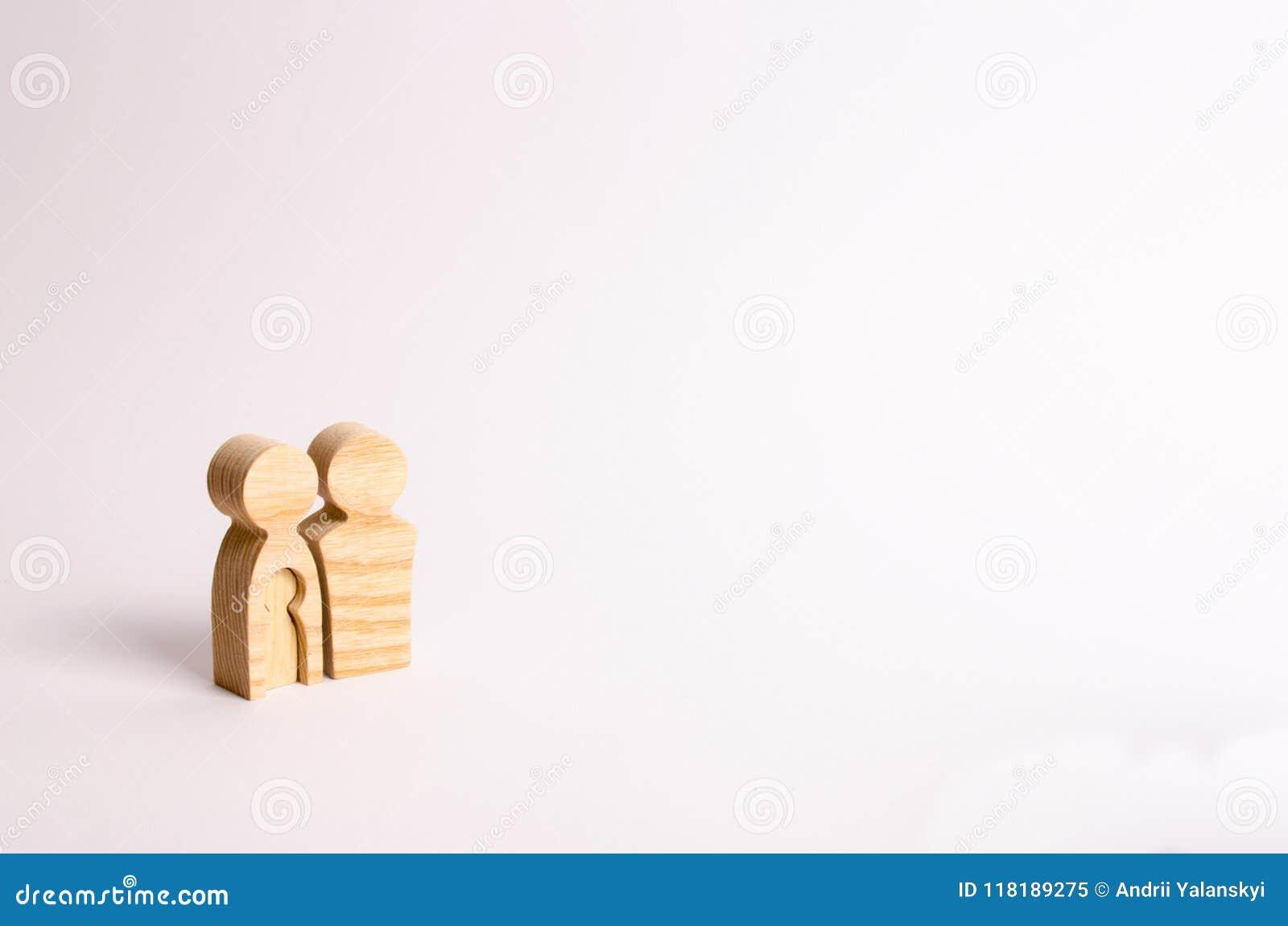 Les figurines en bois des parents se tiennent sur un fond blanc Concept de grossesse, jeune famille Planification pour la famille