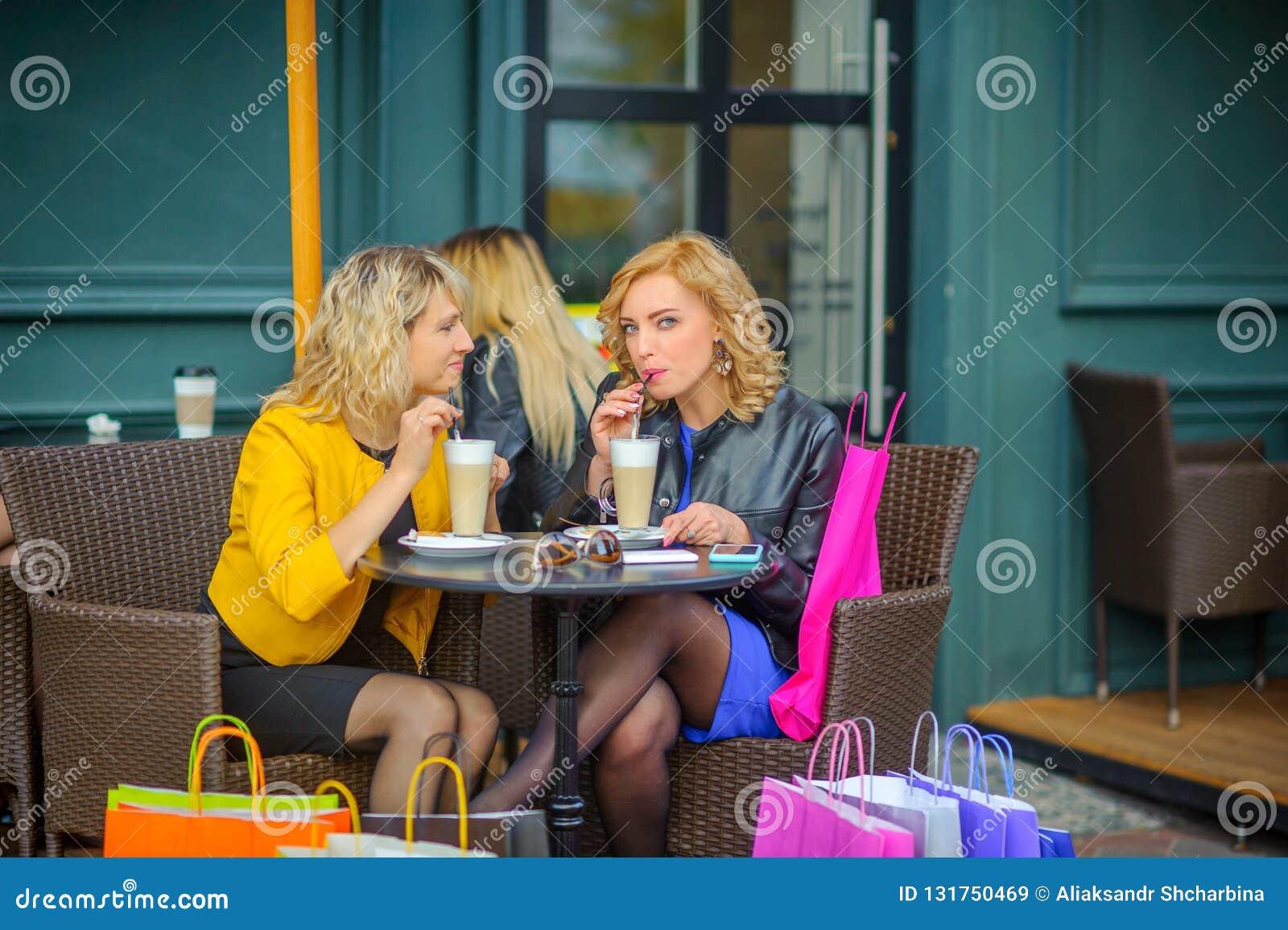 Les filles avec des sacs à provisions s asseyent à une table dans un café, un café de boissons et un sourire