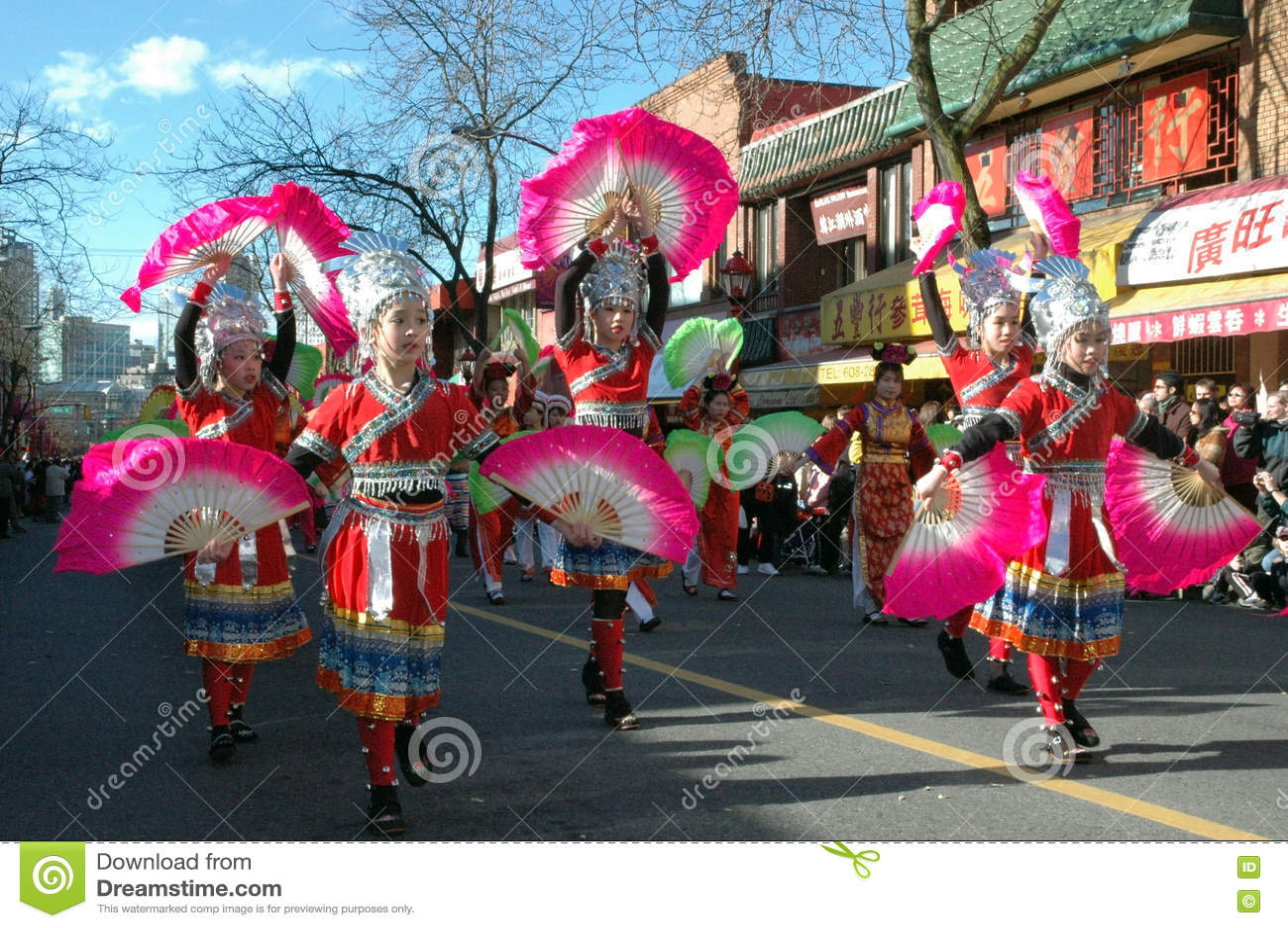 Les filles chinoises avec les fans roses exécutent à Vancouver, défilé de nouvelles années de Chinatown