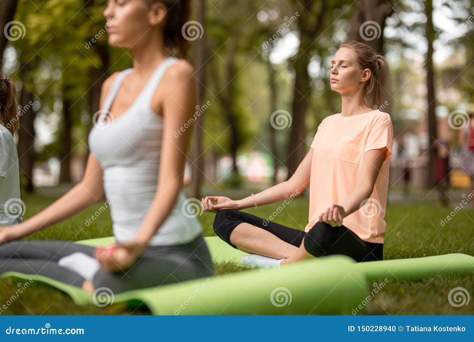 Les filles minces s asseyent en positions de lotus faisant le yoga sur des tapis de yoga sur l herbe verte dans le parc un jour c