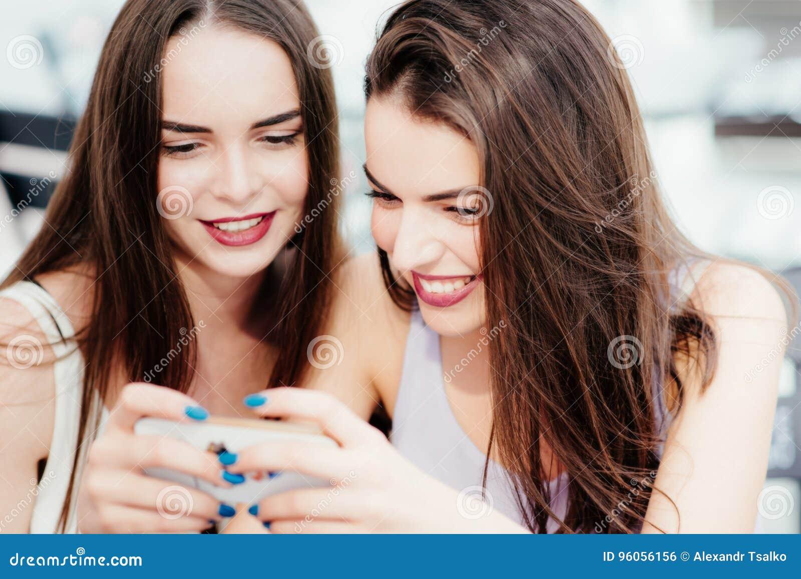Les filles ont l amusement avec un téléphone en café