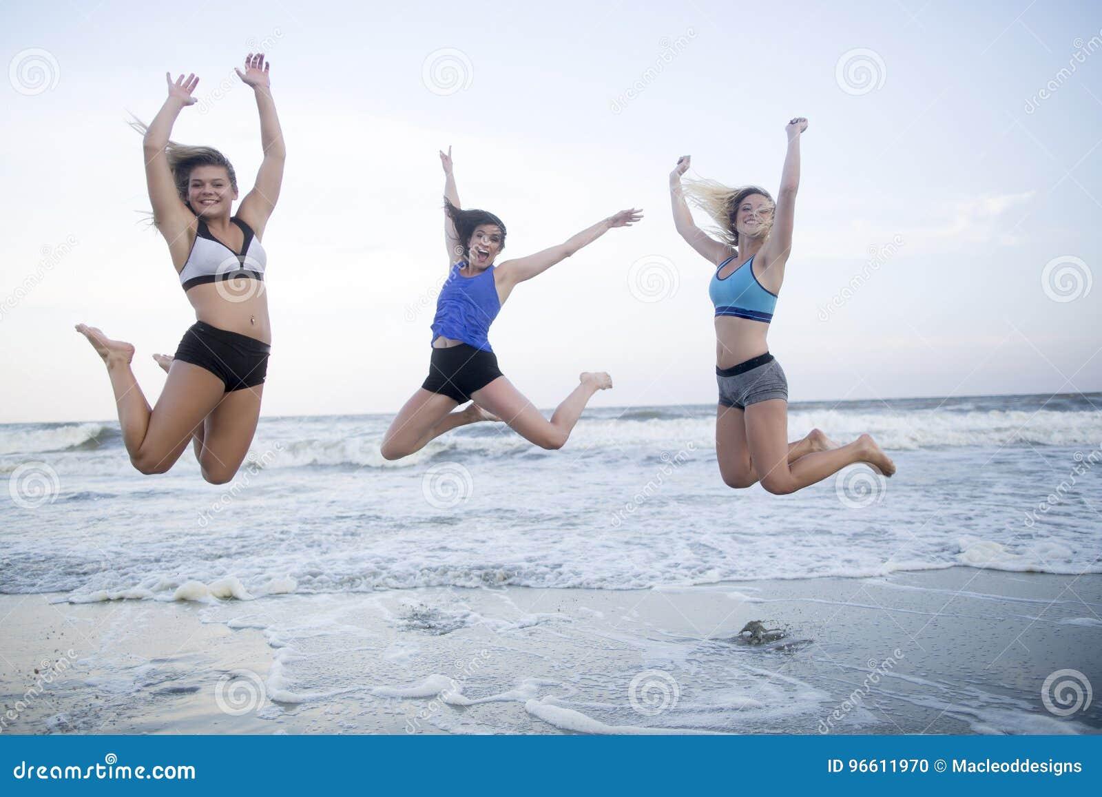 Les filles sautant sur la plage