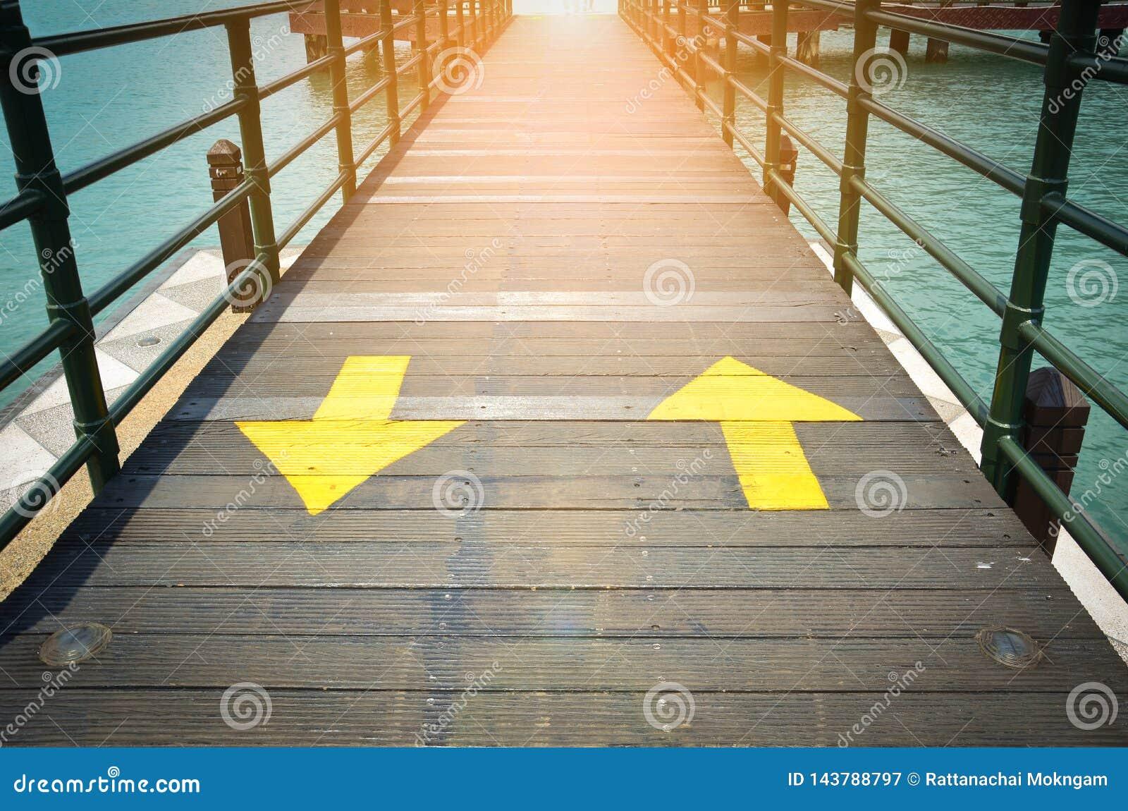 Les flèches jaunes bi-directionnelles du trafic signent l indication la direction deux sur le pont en bois