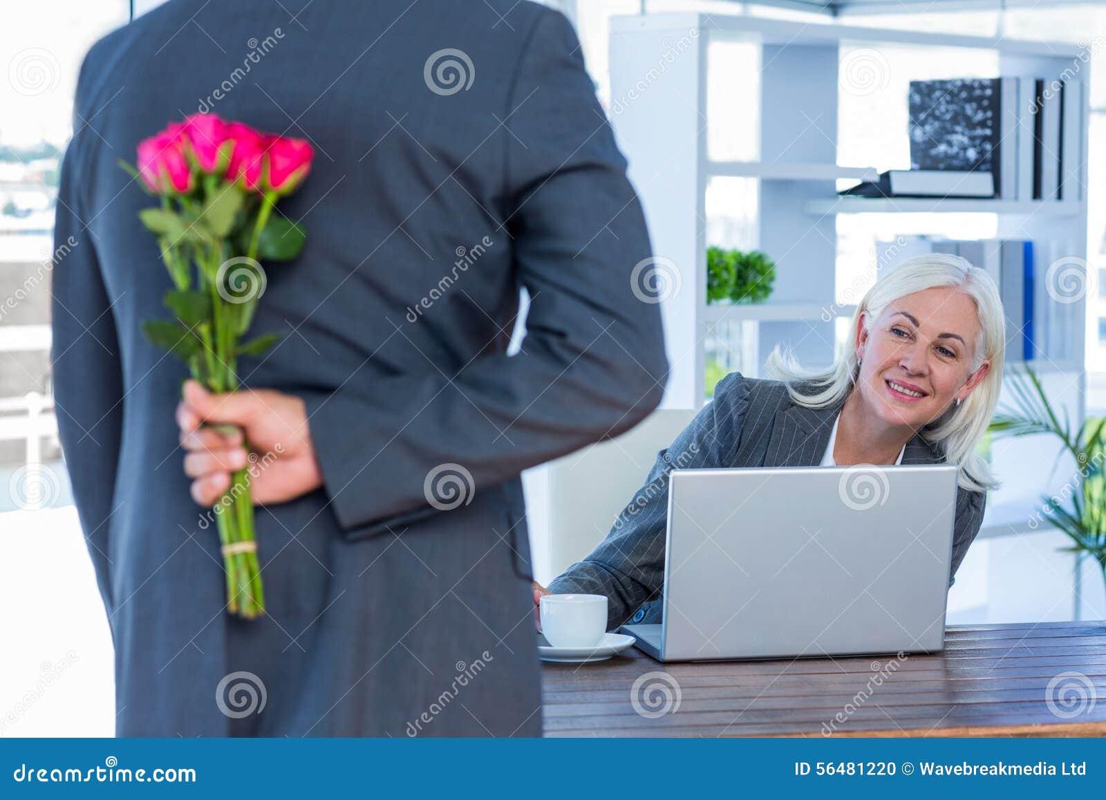 Les fleurs de dissimulation d homme d affaires derrière soutiennent pour le collègue