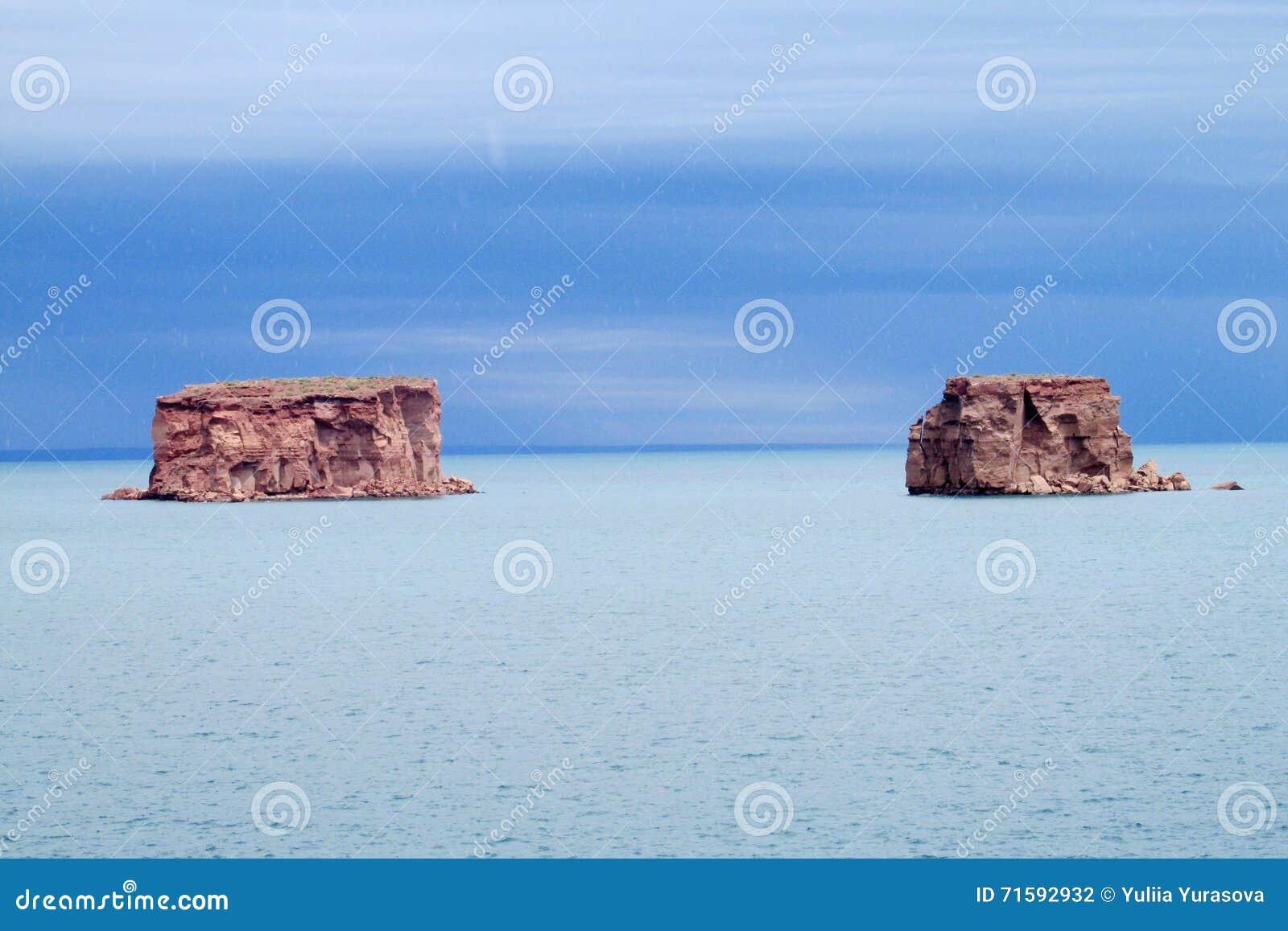 Les formations de roche rouges dans le lac bleu arrosent