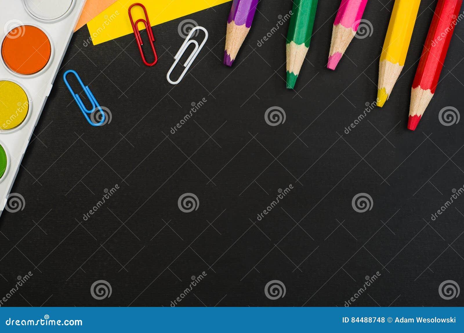 Les fournitures scolaires encadrent au fond noir de tableau Photographie de vue supérieure