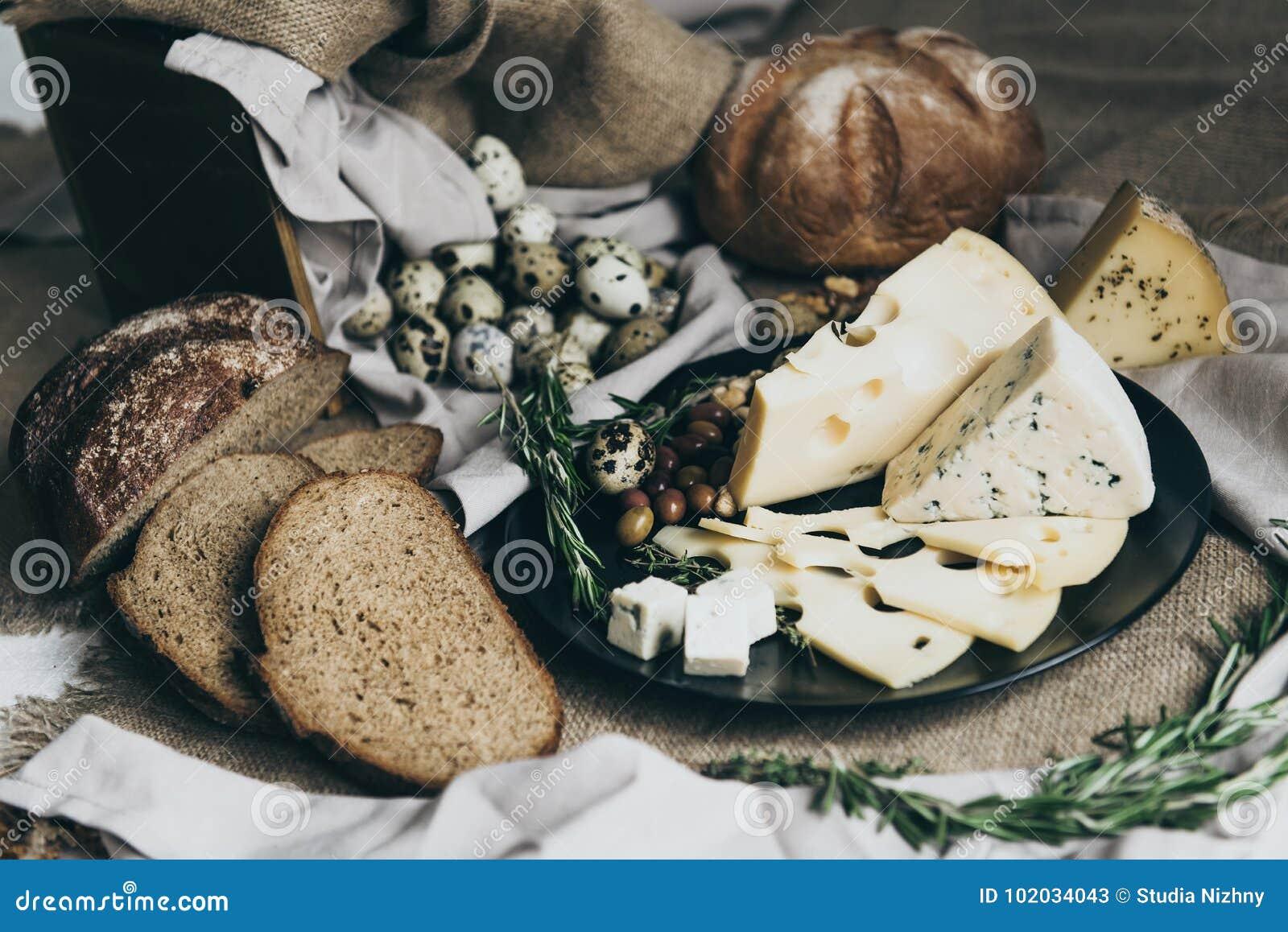 Les fromages se trouvant sur le plat et le pain noirs ont situé tout près Fromage bleu, fromage avec des trous décorés des herbes