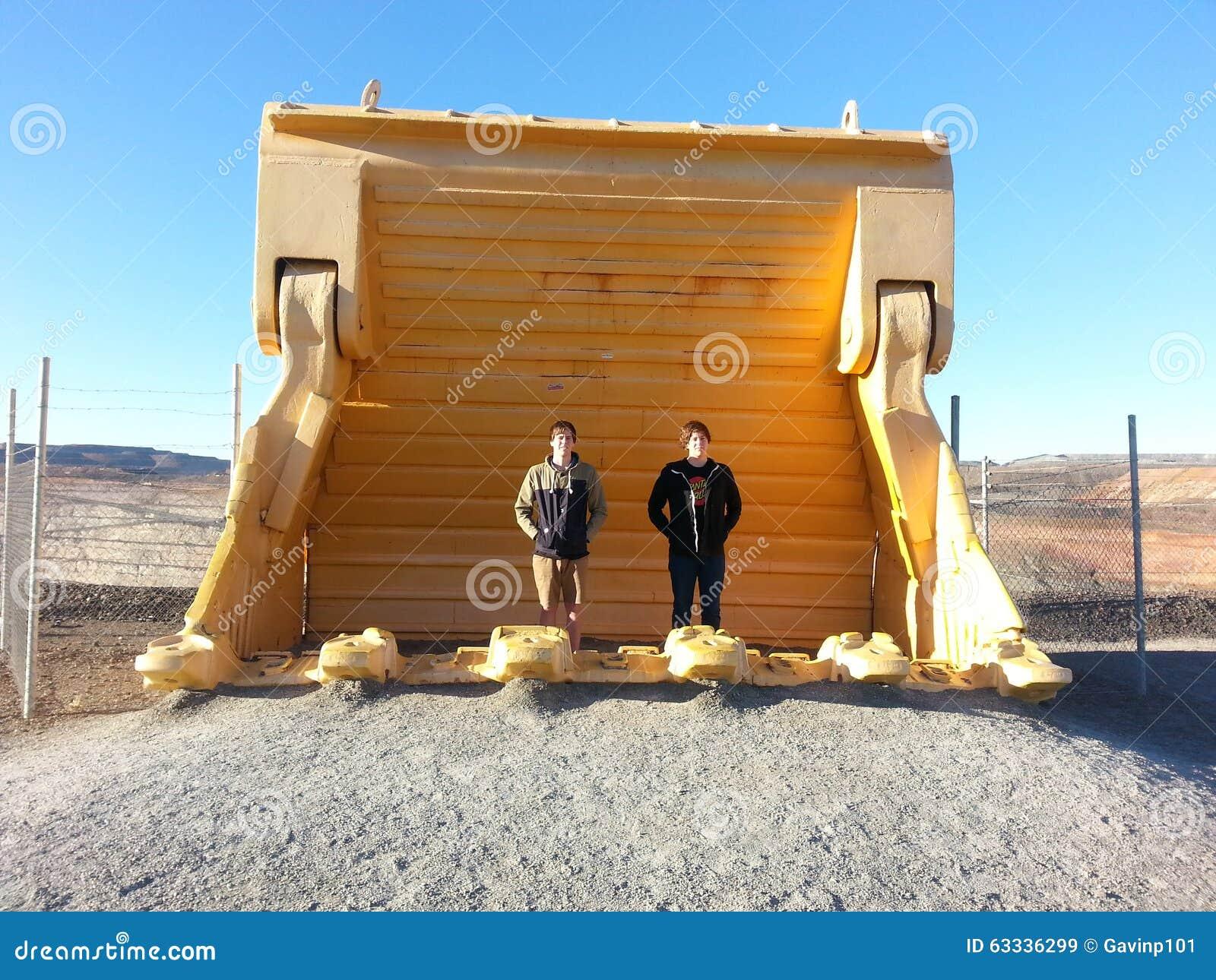 Les garçons de l adolescence se tenant dans l excavatrice énorme d exploitation bucket