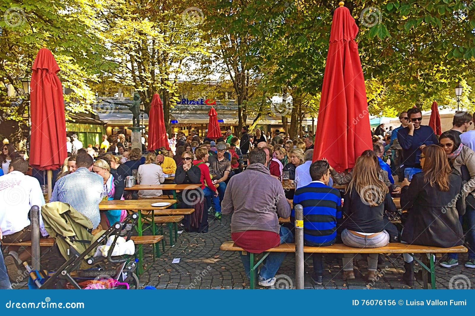Les gens asseyent et causent au jardin de bière dans Viktualienmarkt, Munich