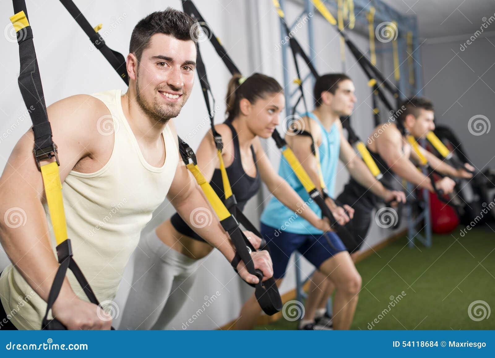Les gens au gymnase faisant les exercices élastiques de corde